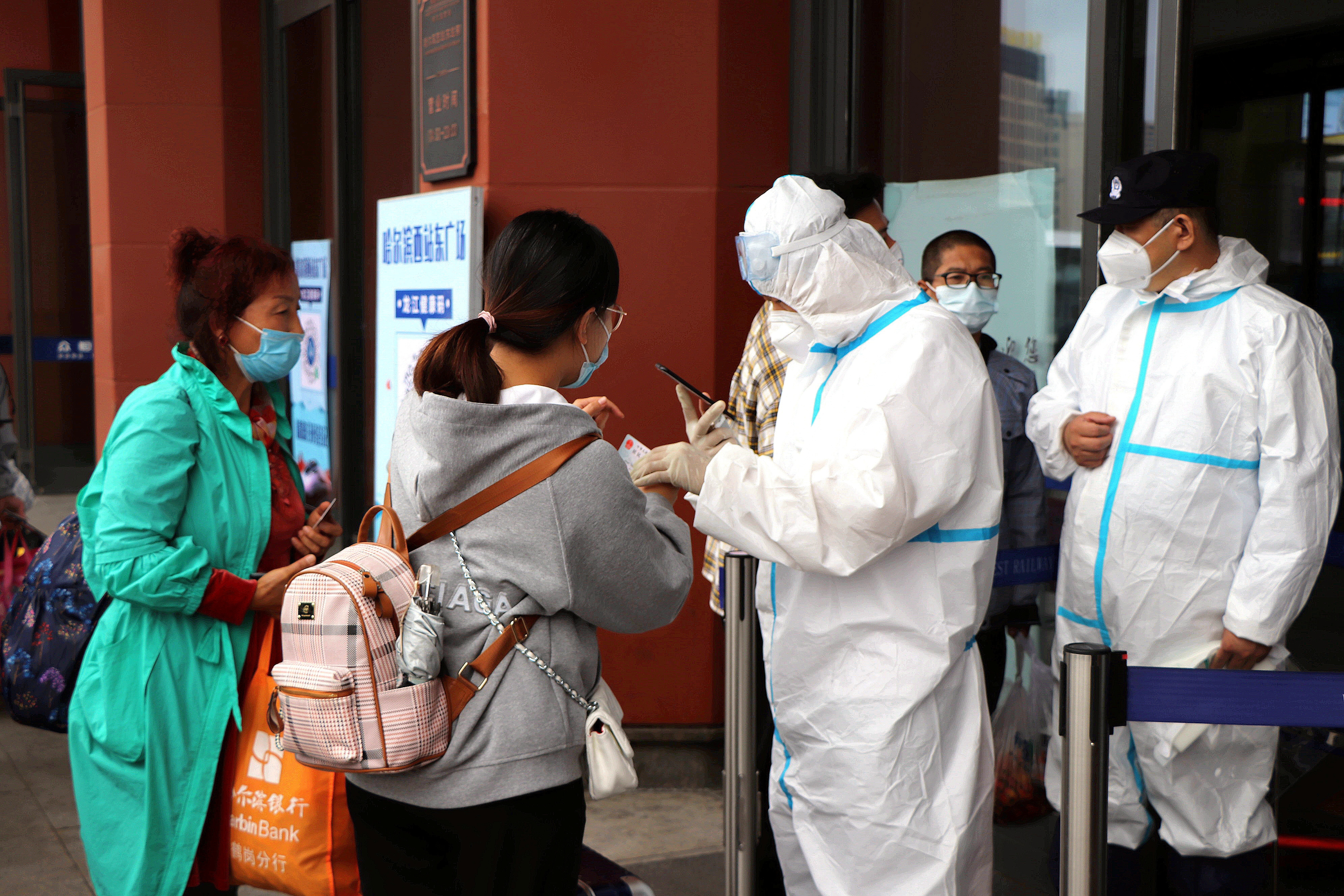 Staff members in protective suits check proof of negative test results for travellers at an entrance to the Harbin West Railway Station following new local cases of the coronavirus disease (COVID-19) in Harbin, Heilongjiang province, China September 22, 2021. cnsphoto via REUTERS ATTENTION EDITORS - THIS IMAGE WAS PROVIDED BY A THIRD PARTY. CHINA OUT.