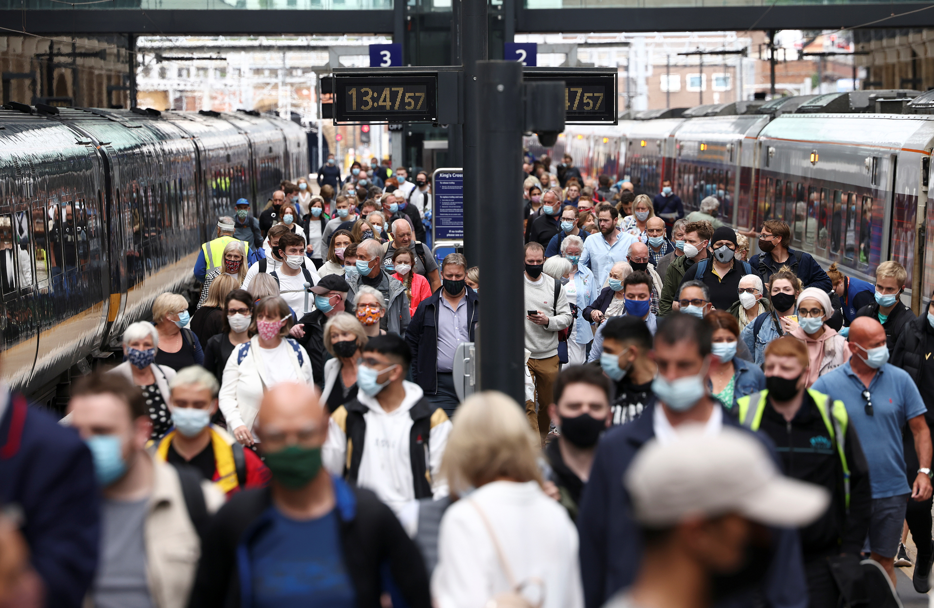 People wearing protective face masks walk along a platform at King's Cross Station, amid the coronavirus disease (COVID-19) outbreak in London, Britain, July 12, 2021. REUTERS/Henry Nicholls