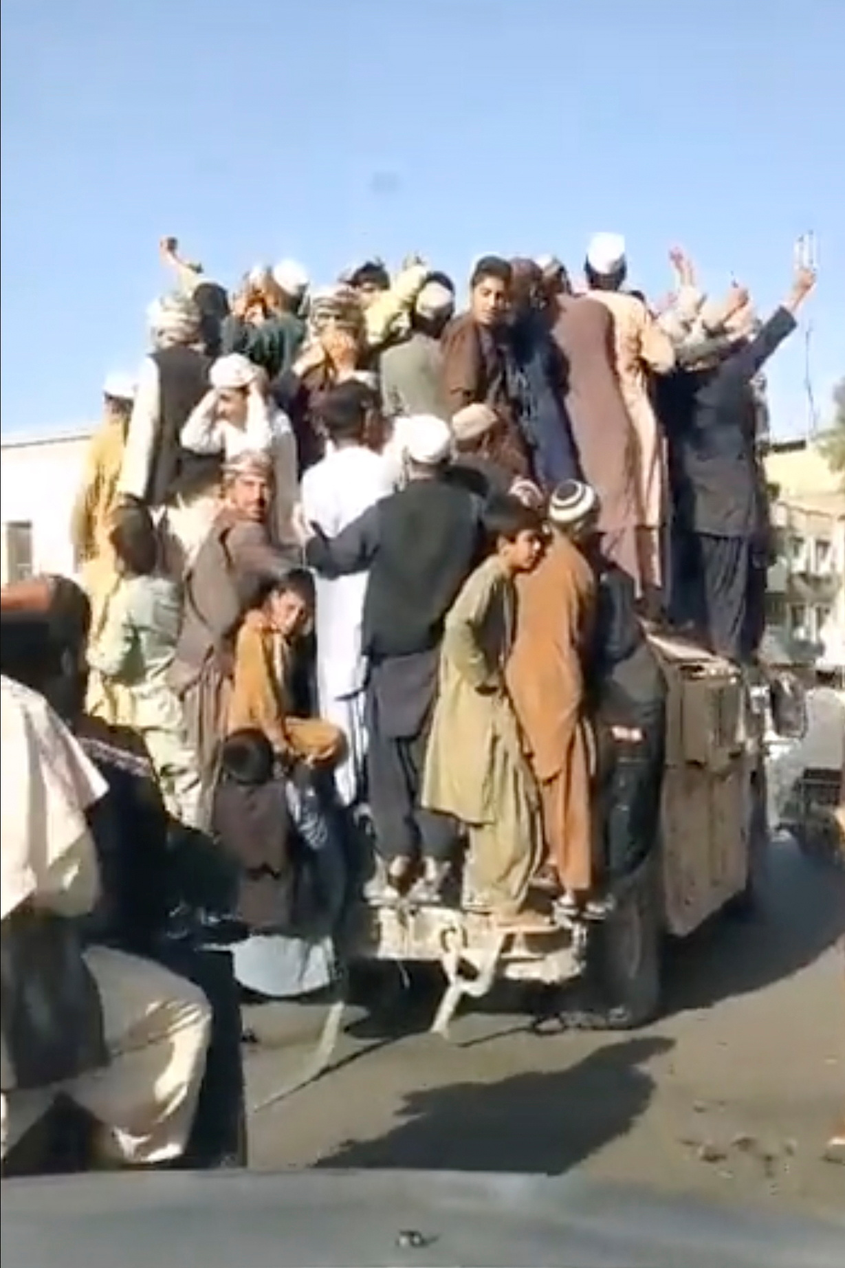 People standing atop an armored vehicle celebrate as it drives through Shaheedan Square, in the city of Kandahar, Afghanistan in this screen grab taken from a video from social media uploaded on August 13, 2021. TALIBAN HANDOUT/via REUTERS  THIS IMAGE HAS BEEN SUPPLIED BY A THIRD PARTY.