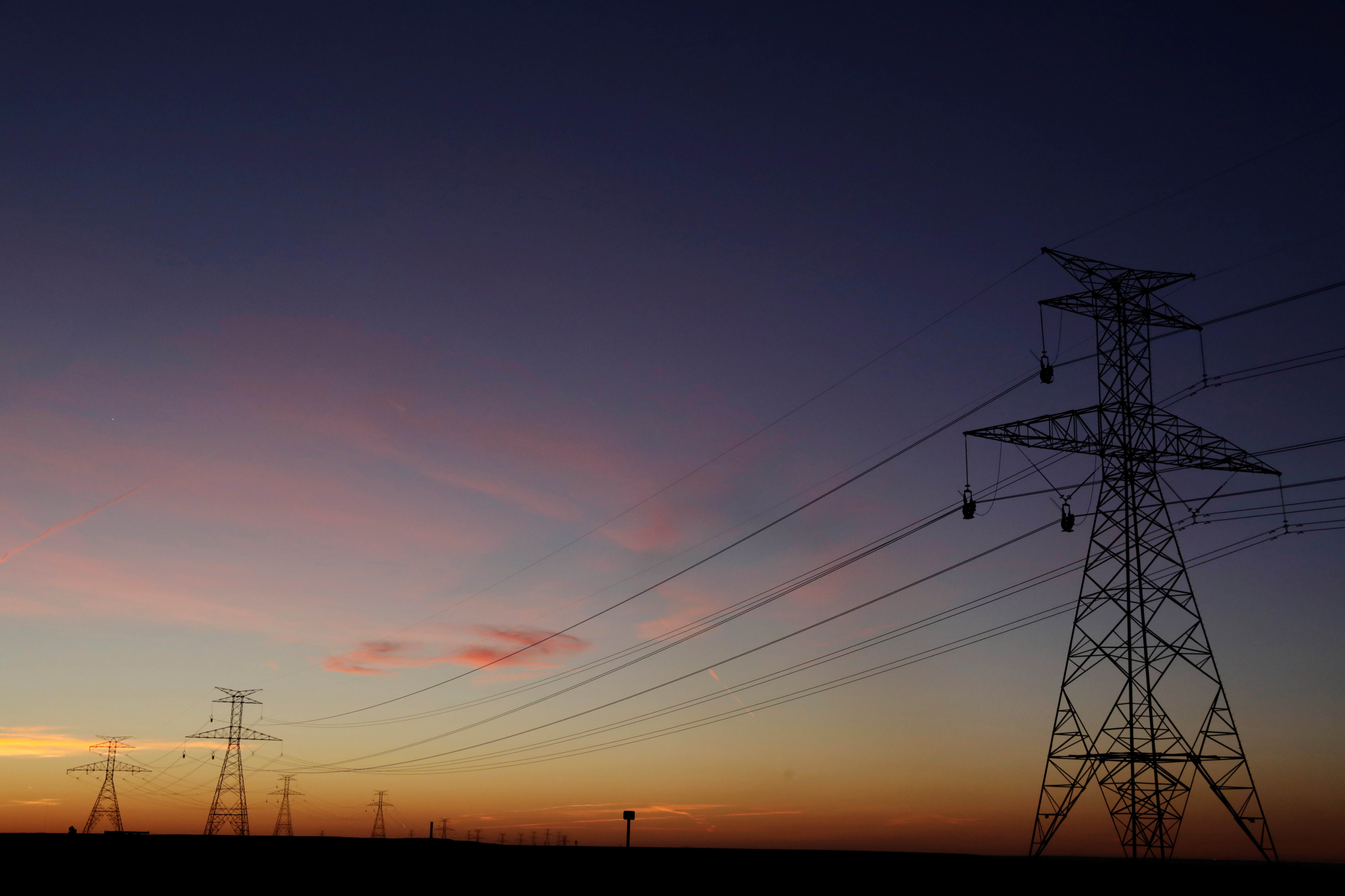 The sun sets behind power lines above the plains north of Amarillo, Texas, U.S., March 14, 2017. REUTERS/Lucas Jackson
