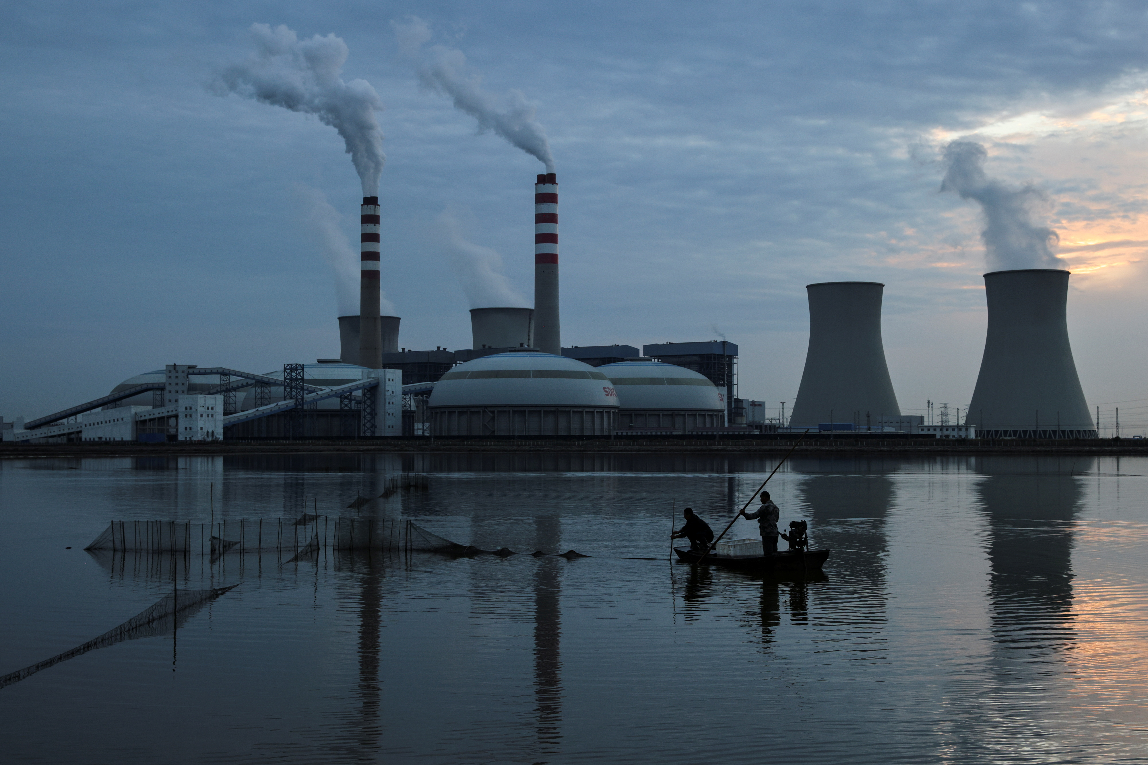 Fishermen sail a boat past a power plant of the State Development and Investment Corporation (SDIC) outside Tianjin, China, October 14, 2021. REUTERS/Thomas Peter