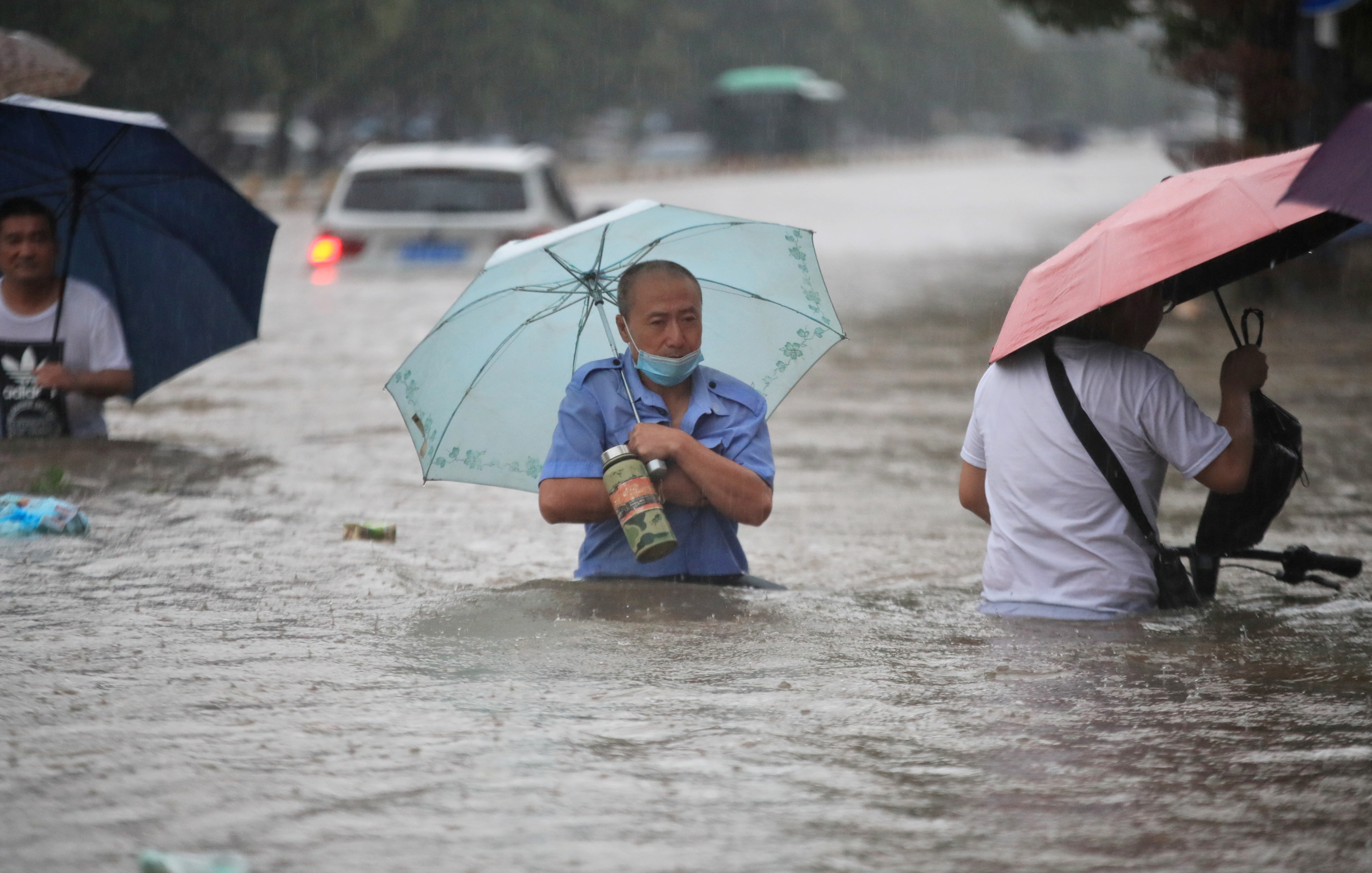 Residents wade through floodwaters on a flooded road amid heavy rainfall in Zhengzhou, Henan province, China July 20, 2021. Picture taken July 20, 2021. China Daily via REUTERS  ATTENTION EDITORS - THIS IMAGE WAS PROVIDED BY A THIRD PARTY. CHINA OUT.