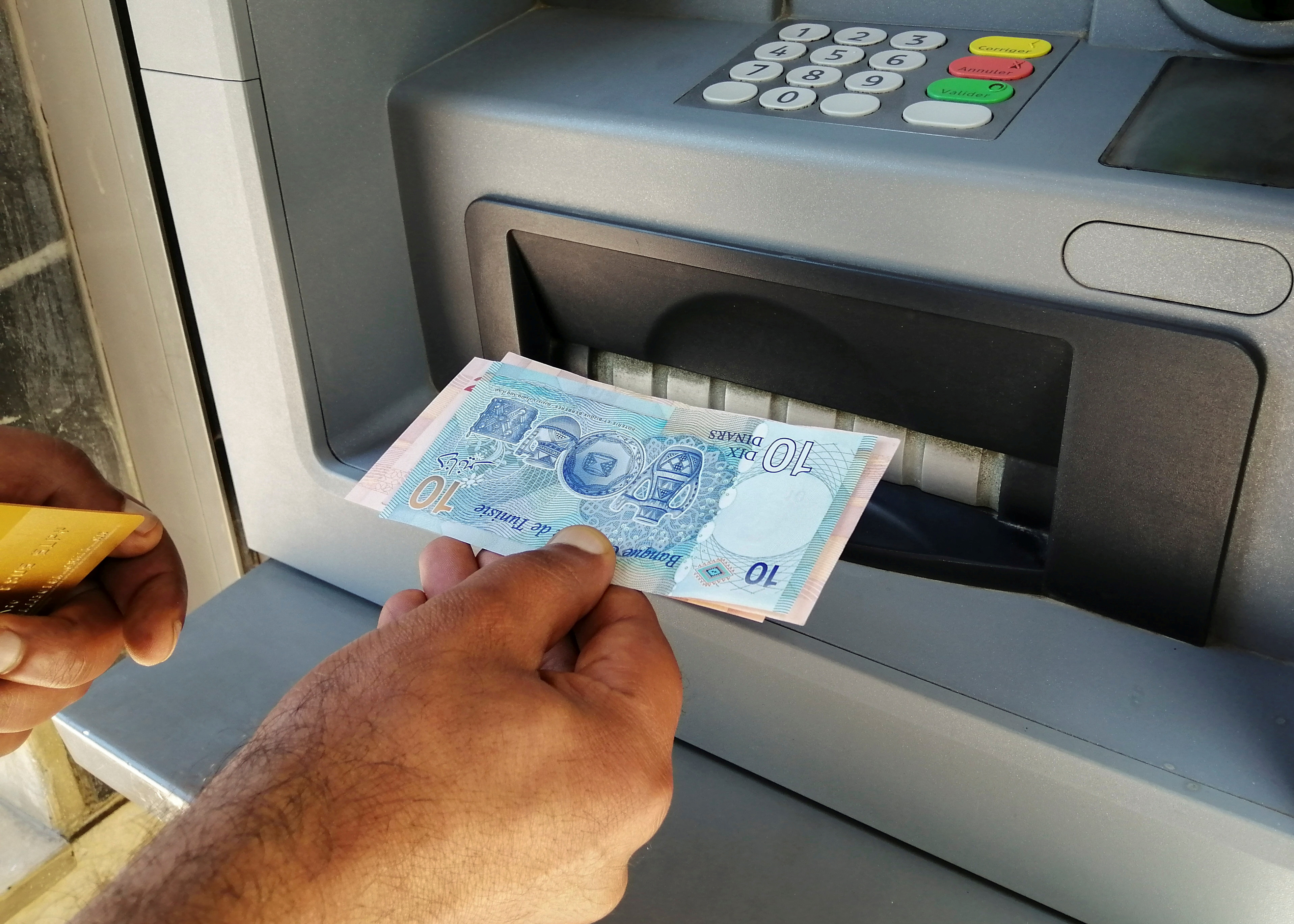 A man displays Tunisian dinar banknotes after withdrawing cash from an ATM machine in Tunis, Tunisia, May 25, 2021. Picture taken May 25, 2021. REUTERS/Jihed Abidellaoui/File Photo
