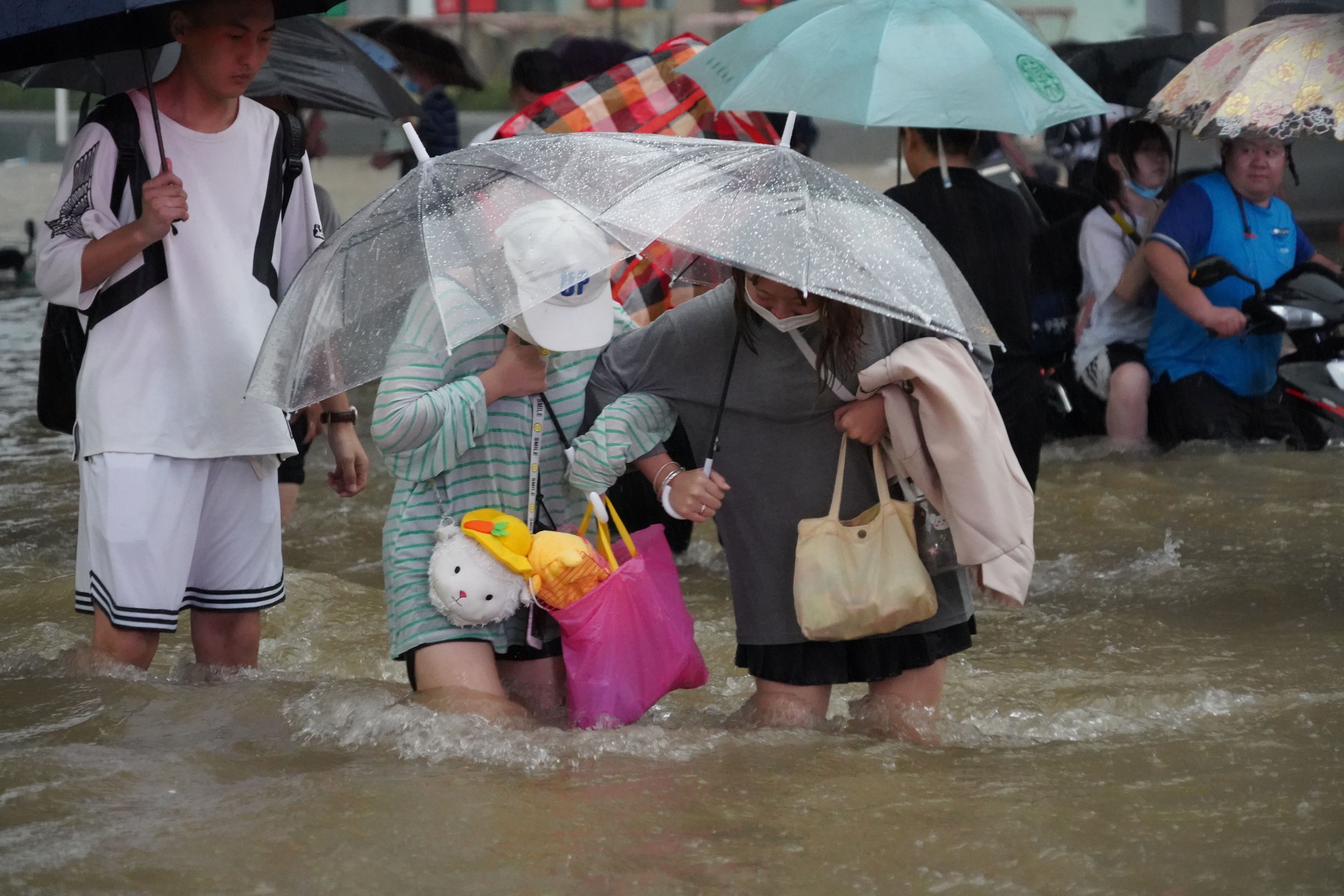 Residents, holding umbrellas amid heavy rainfall, wade through floodwaters on a road in Zhengzhou, Henan province, China July 20, 2021. Picture taken July 20, 2021. cnsphoto via REUTERS   ATTENTION EDITORS - THIS IMAGE WAS PROVIDED BY A THIRD PARTY. CHINA OUT.
