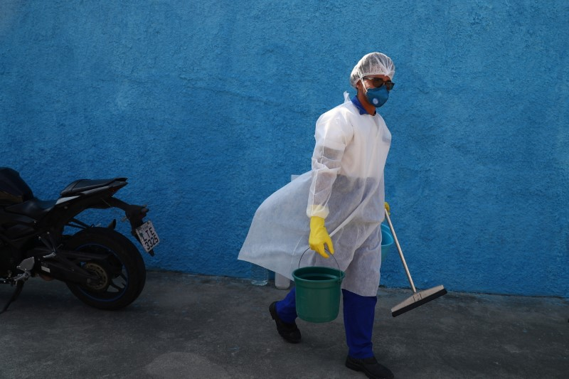 A cleaning worker prepares to disinfect an Emergency Mobile Care Service (SAMU) ambulance after taking a suspected COVID-19 patient, amid the coronavirus disease (COVID-19) outbreak, in the Moacyr do Carmo hospital in Duque de Caxias near Rio de Janeiro, Brazil May 20, 2021. REUTERS/Pilar Olivares