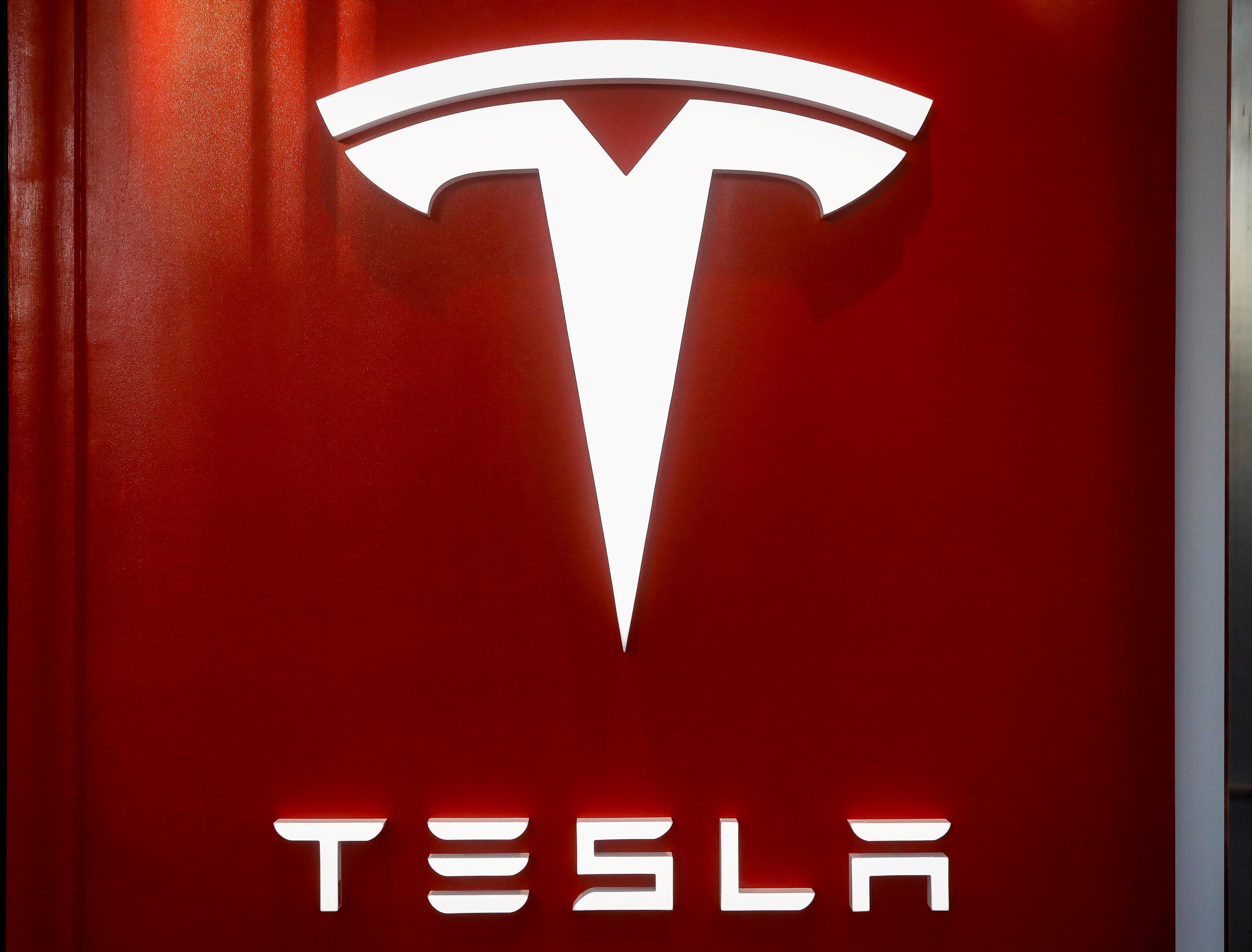 The Tesla logo is seen at the entrance to Tesla Motors' showroom in Manhattan's Meatpacking District in New York City, U.S., December 14, 2017. REUTERS/Brendan McDermid/File Photo