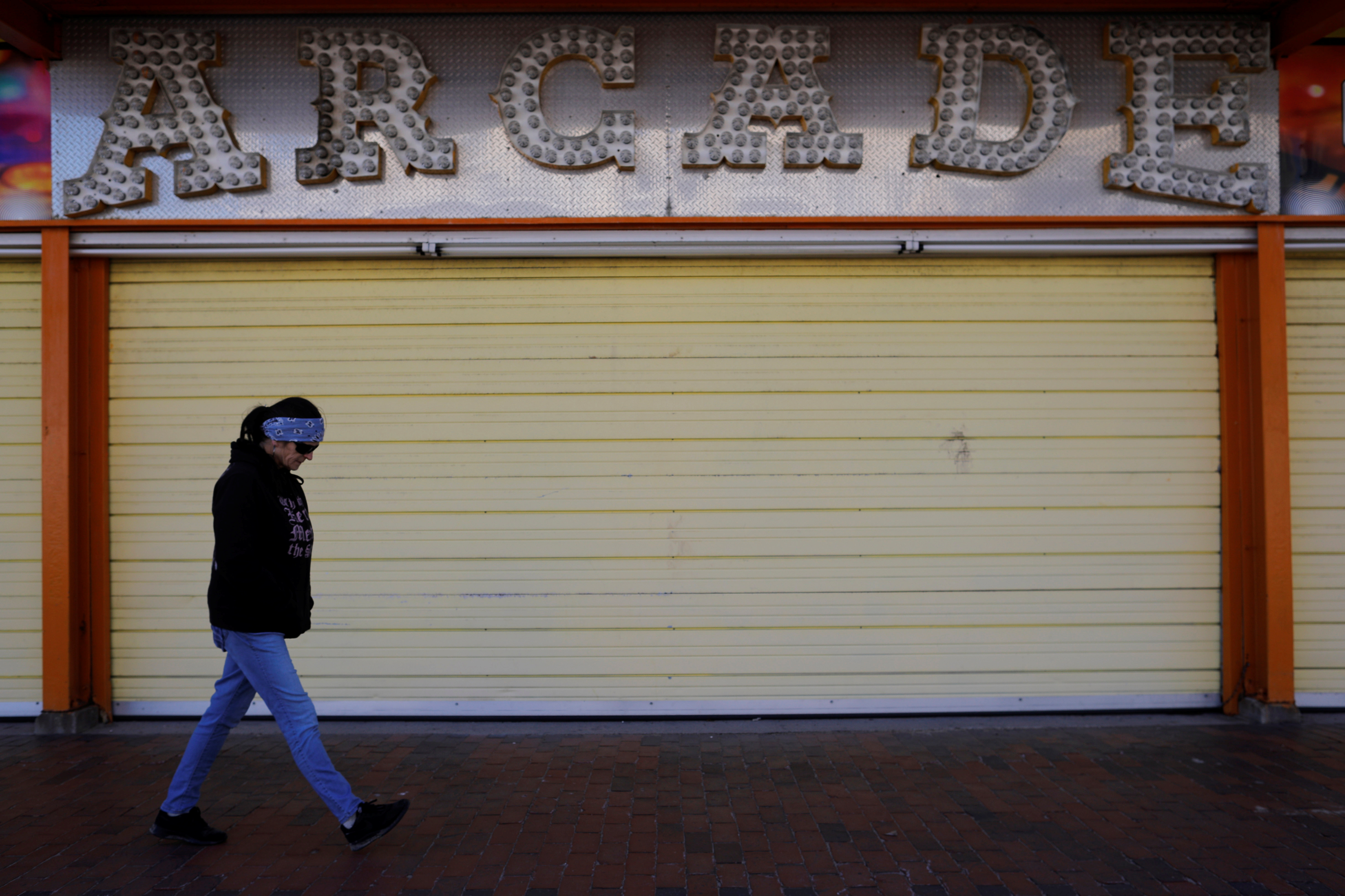 A woman walks past the arcade closed amid the coronavirus disease (COVID-19) outbreak in Old Orchard Beach, Maine, U.S., April 25, 2020. REUTERS/Brian Snyder