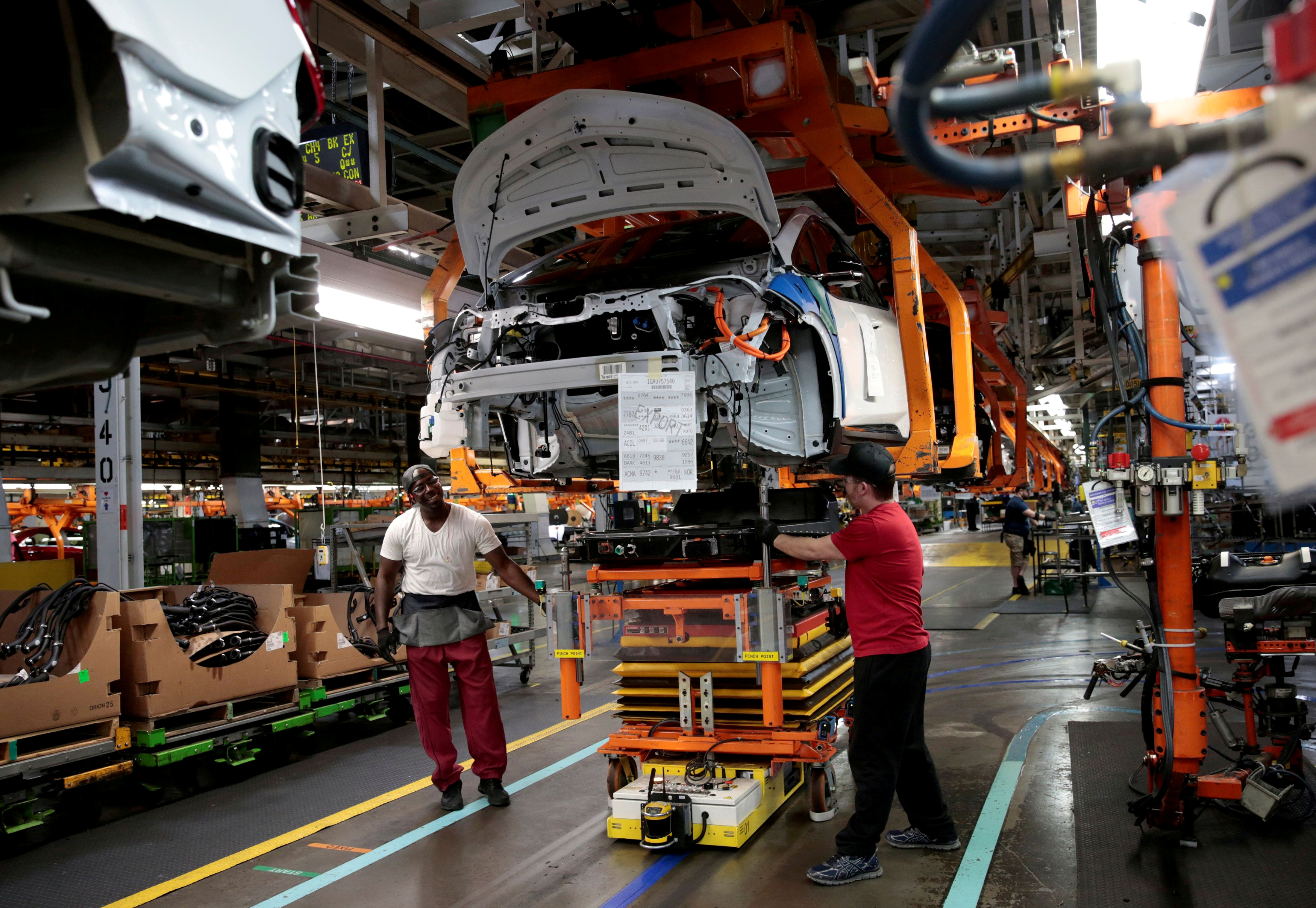 General Motors assembly workers connect a battery pack underneath a partially assembled 2018 Chevrolet Bolt EV vehicle on the assembly line at Orion Assembly in Lake Orion, Michigan, U.S., March 19, 2018.   REUTERS/Rebecca Cook