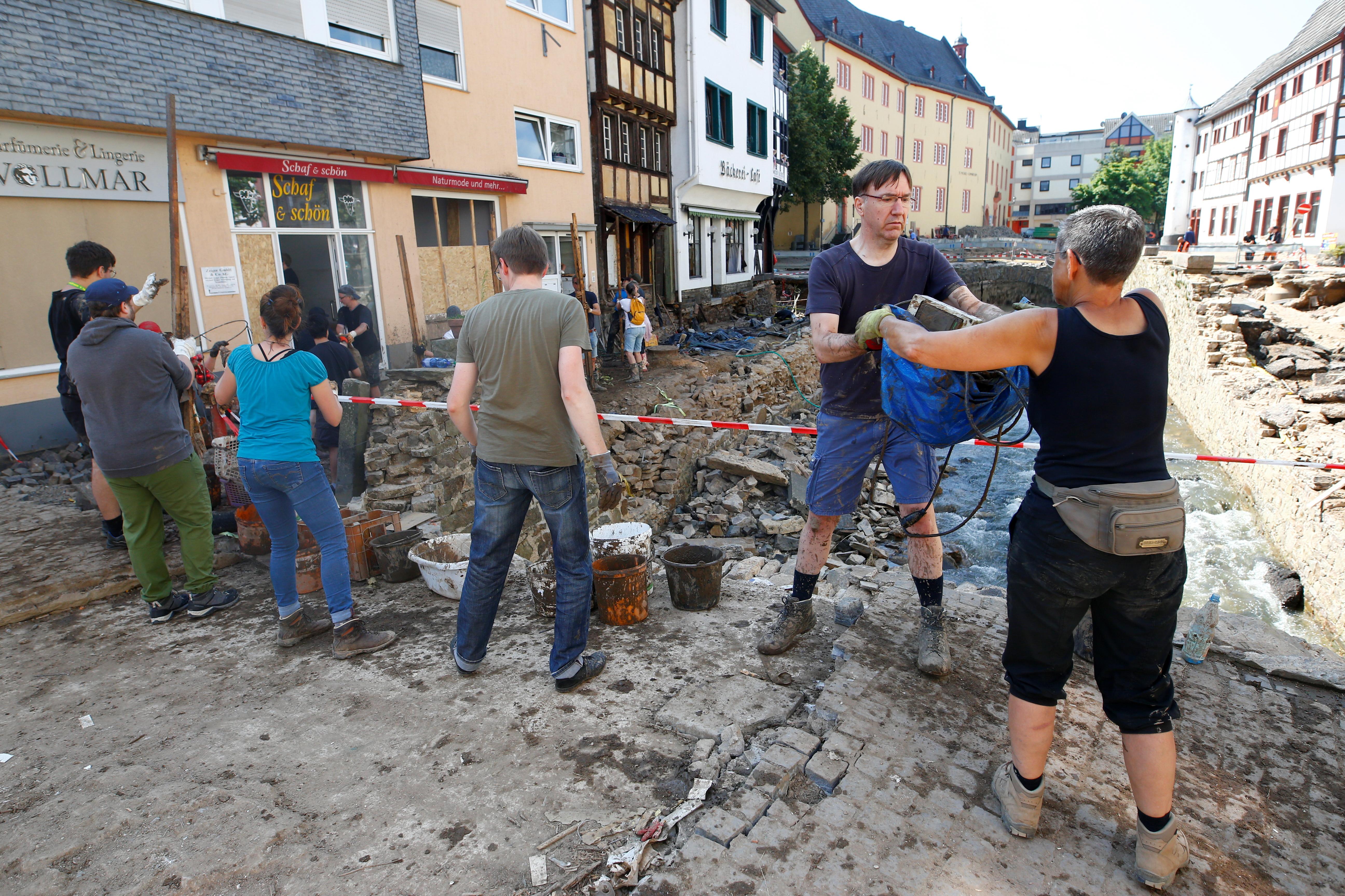 Ljudi uklanjaju smeće i smeće, nakon obilnih kiša, u Bad Muenstereifelu, sjeverna Rajna-Vestfalija, Njemačka, 21. srpnja 2021. REUTERS / Thilo Schmuelgen