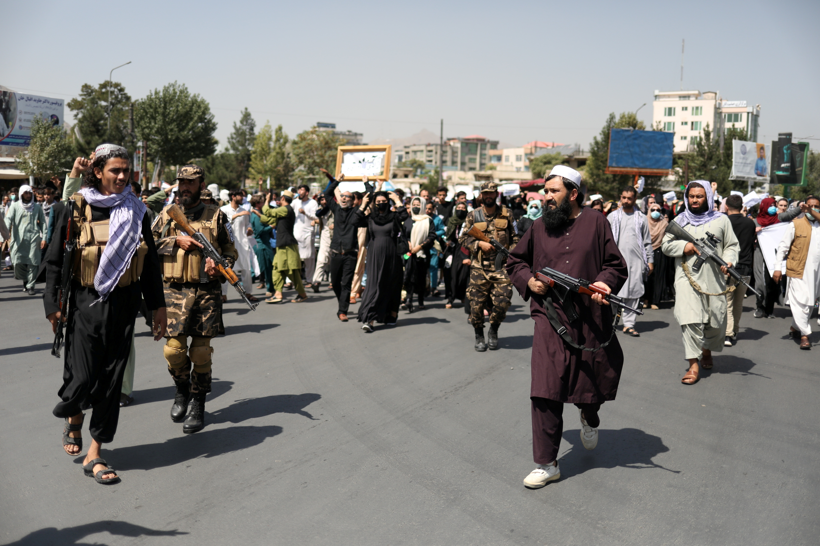 Taliban soldiers stand in front of protesters during the anti-Pakistan protest in Kabul, Afghanistan, September 7, 2021. WANA (West Asia News Agency) via REUTERS