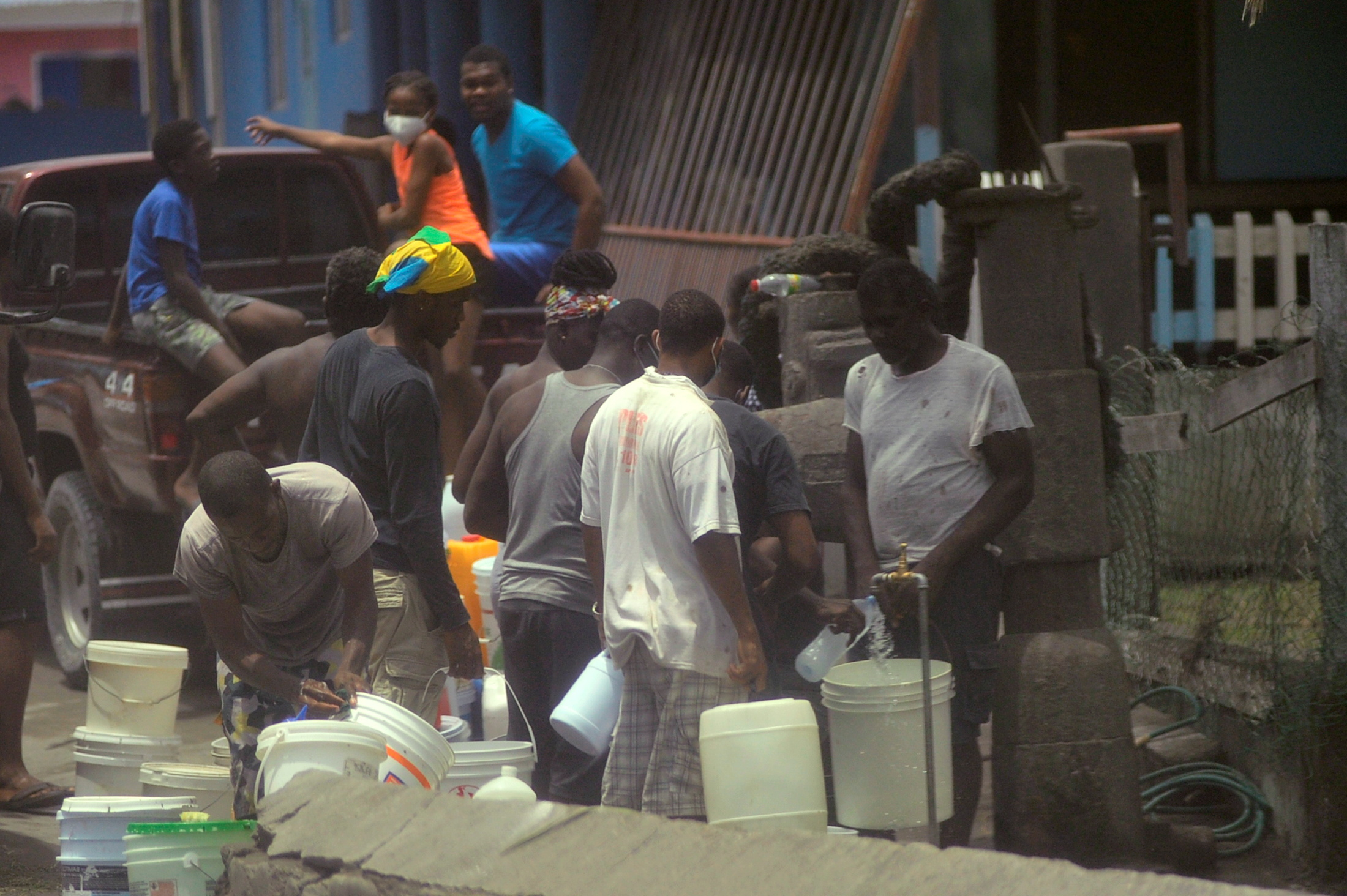 Local residents fill containers of water after a series of eruptions from La Soufriere volcano covered the area with a thick layer of ash in Biabou, Saint Vincent and the Grenadines, April 13, 2021.  REUTERS/Robertson S. Henry