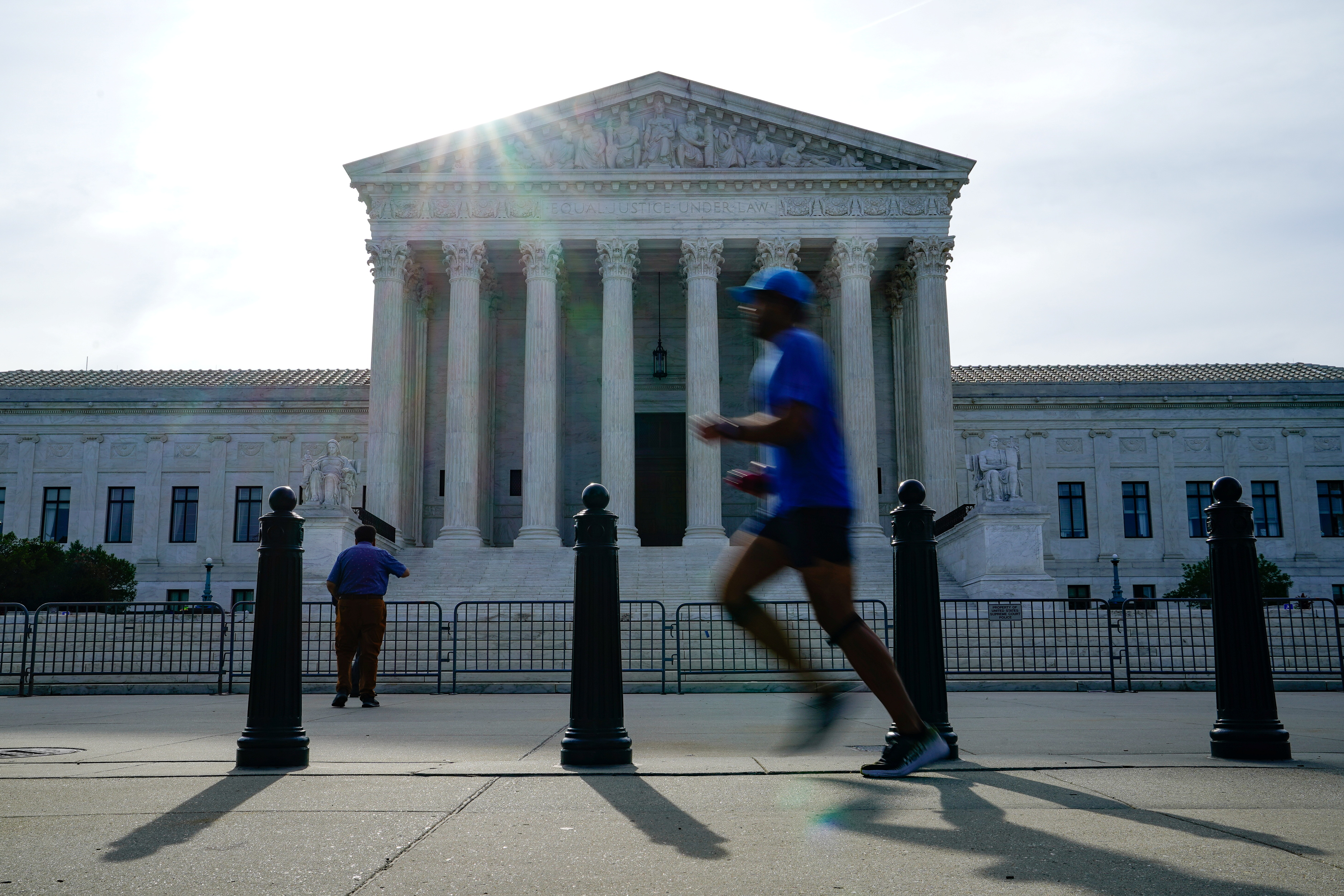People walk past the U.S. Supreme Court the day the court is set to release orders and opinions in Washington, U.S., June 1, 2021. REUTERS/Erin Scott