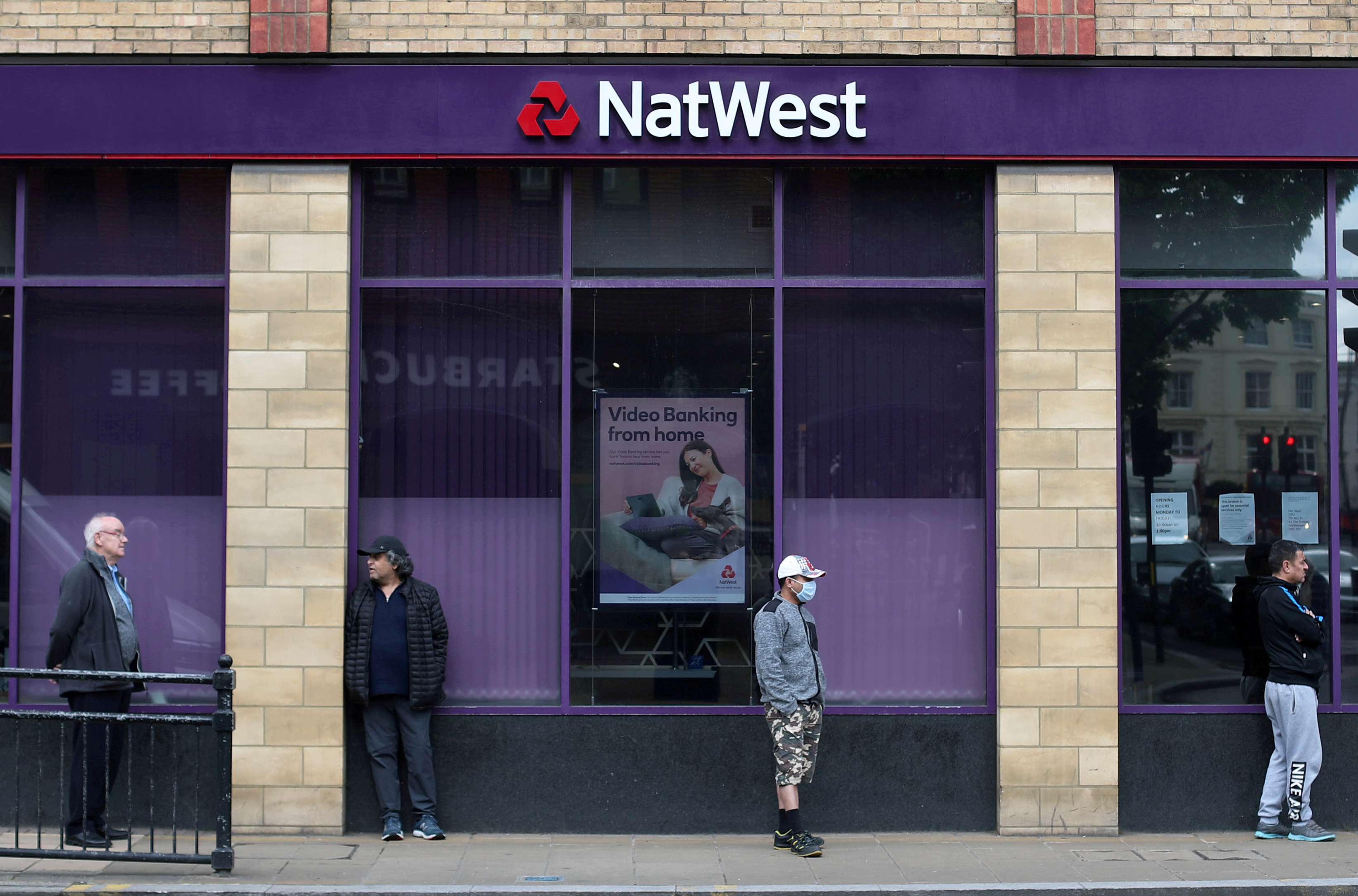 People maintain social distance while they queue outside a Natwest bank in Wimbledon in London, Britain, May 1, 2020. REUTERS/Hannah McKay/File Photo