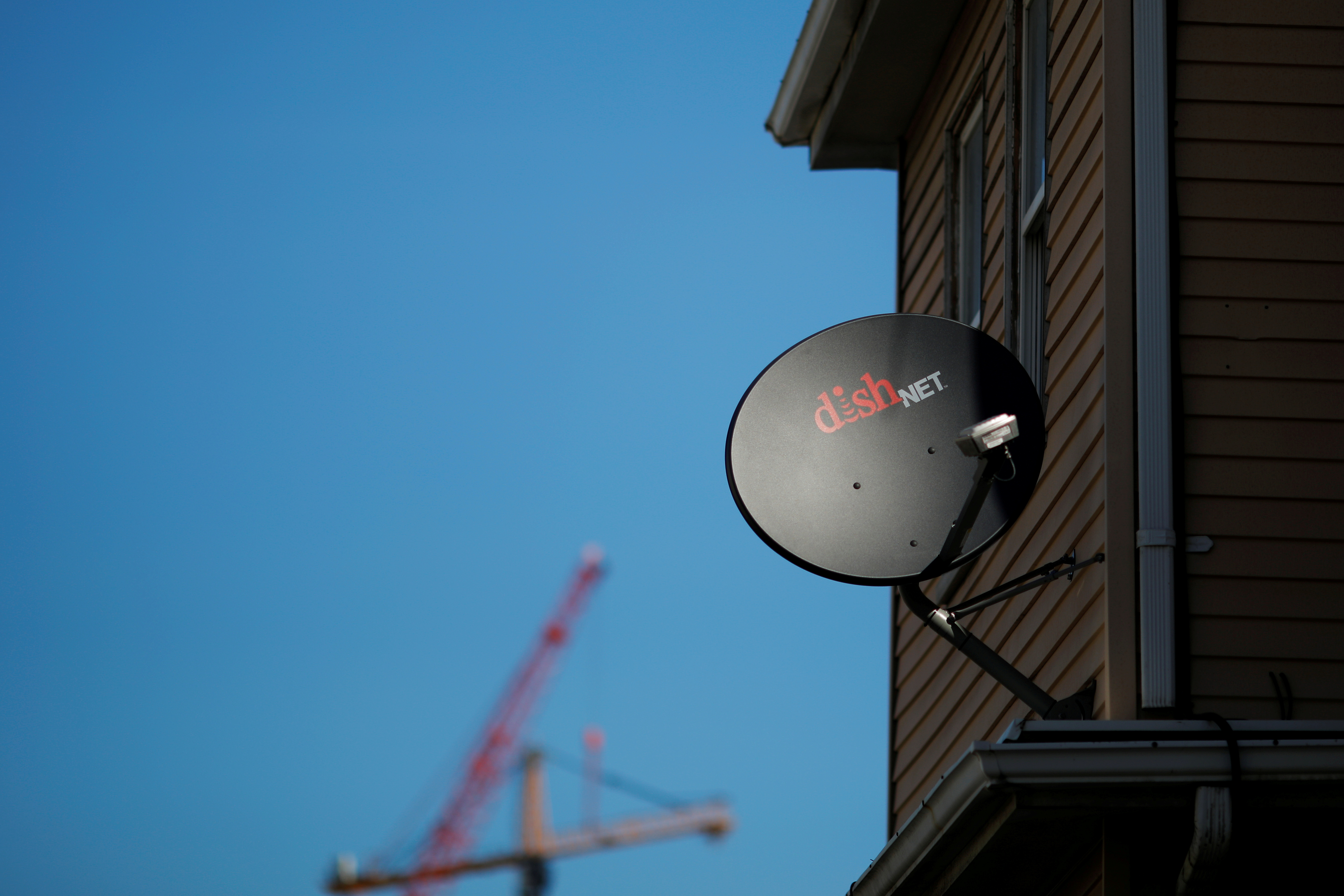 A Dish Network receiver hangs on a house in Somerville, Massachusetts, U.S., February 21, 2017.   REUTERS/Brian Snyder/File Photo