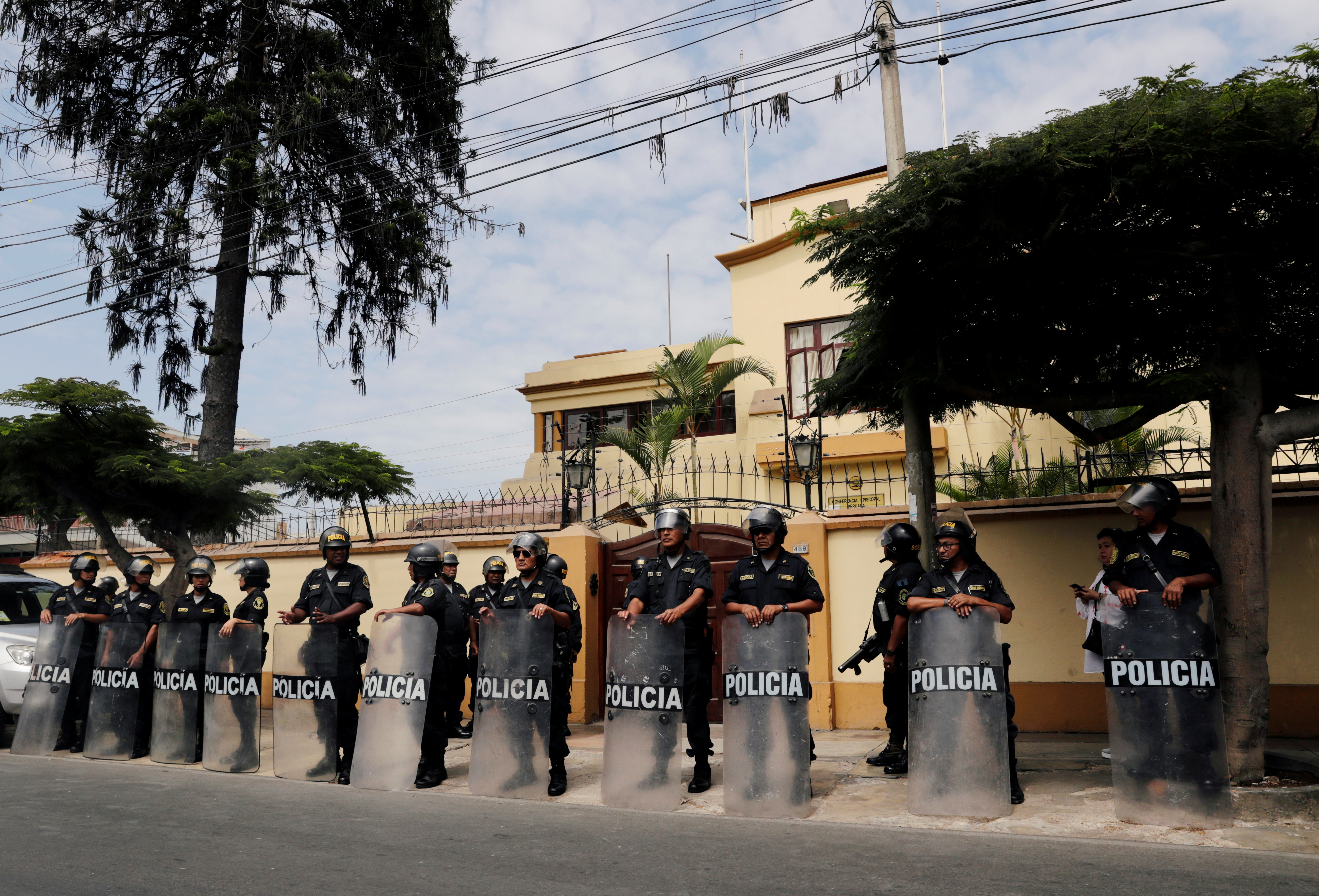 Police officers stand guard outside at the Episcopal Conference of Peru where Gregorio Rojas, president of the community Fuerabamba, Chinese-owned miner MMG Ltd, the Peruvian government and the Catholic Church take part in negotiations, aimed at ending a dispute with an indigenous community that has blocked roads to the company's Las Bambas mine, in Lima, Peru April 6, 2019. REUTERS/Henry Romero/File Photo