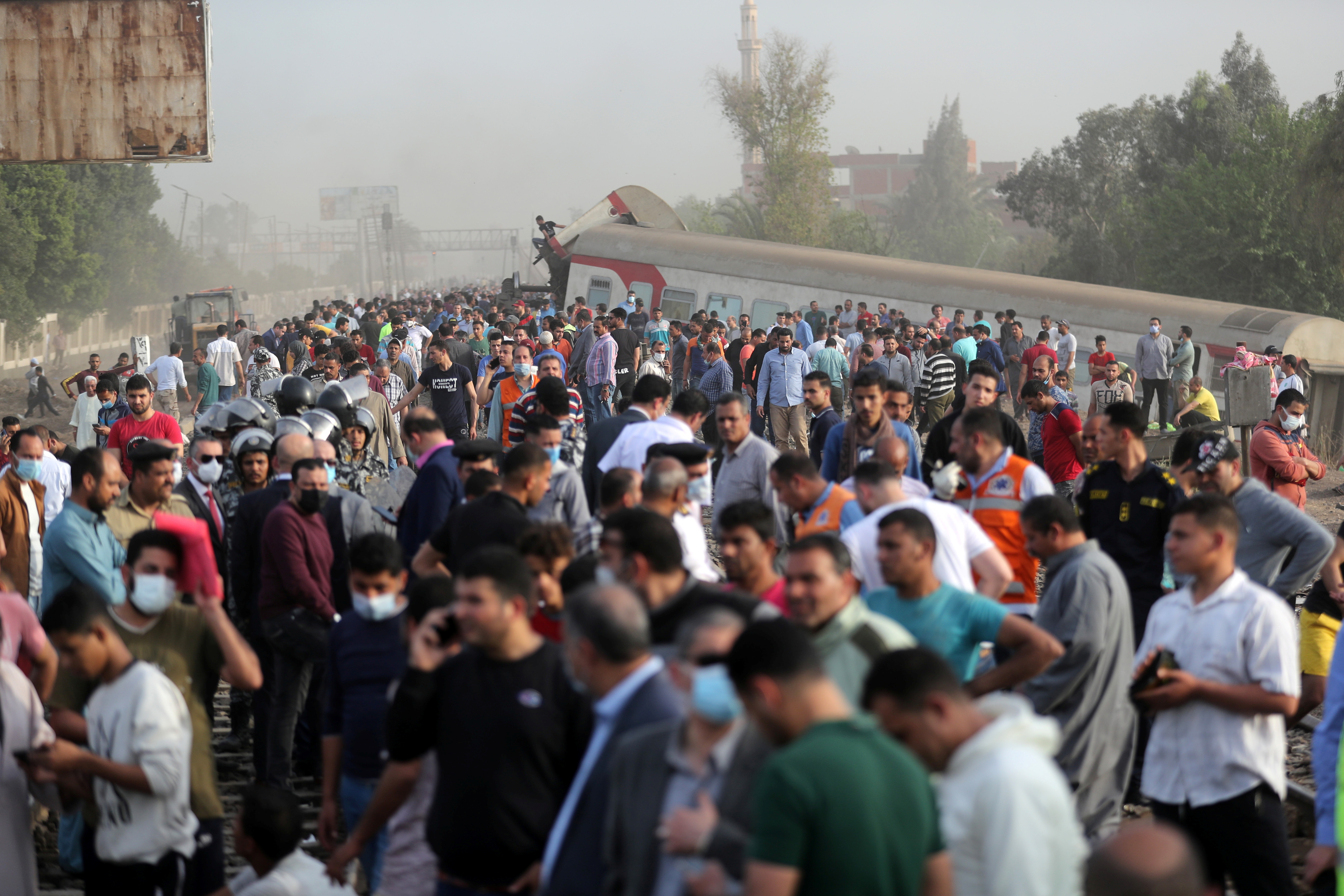 La gente se reúne en el lugar donde descarrilaron los vagones de tren en la provincia de Qalioubia, al norte de El Cairo, Egipto, el 18 de abril de 2021. REUTERS / Mohamed Abd El Ghany