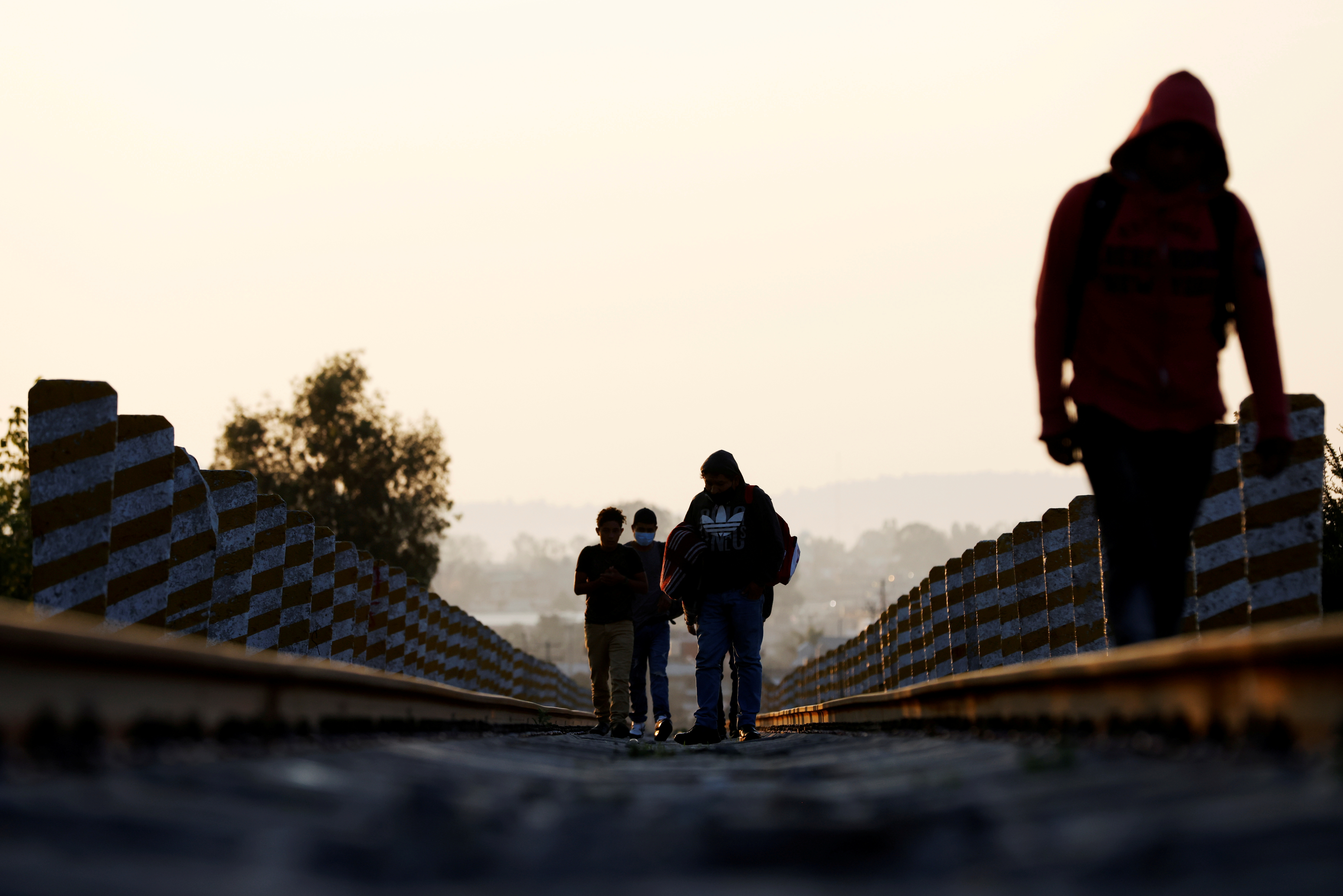 Central American migrants walk on the train track near the