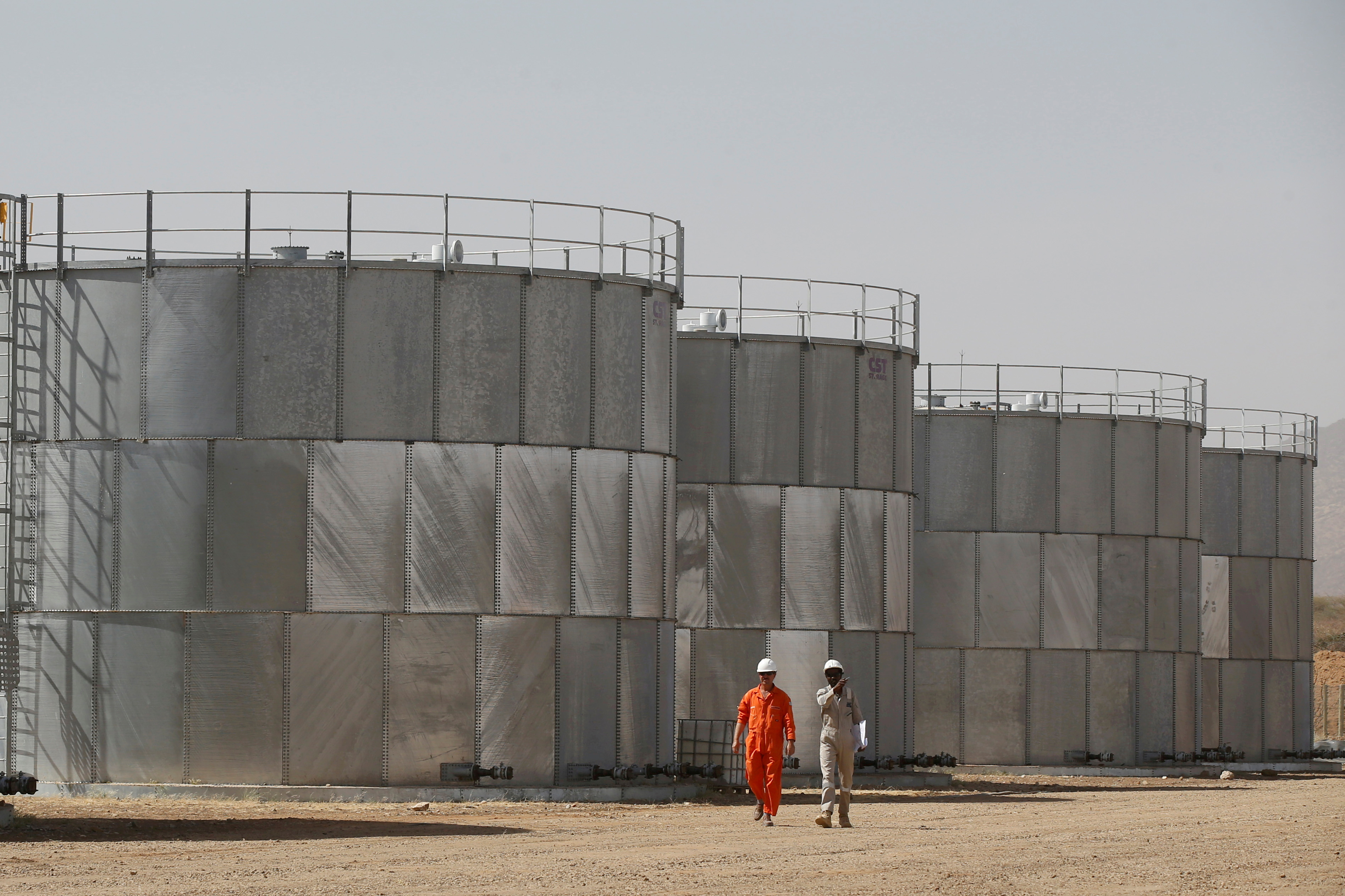 Workers walk past storage tanks at Tullow Oil's Ngamia 8 drilling site in Lokichar, Turkana County, Kenya, February 8, 2018. REUTERS/Baz Ratner/File Photo