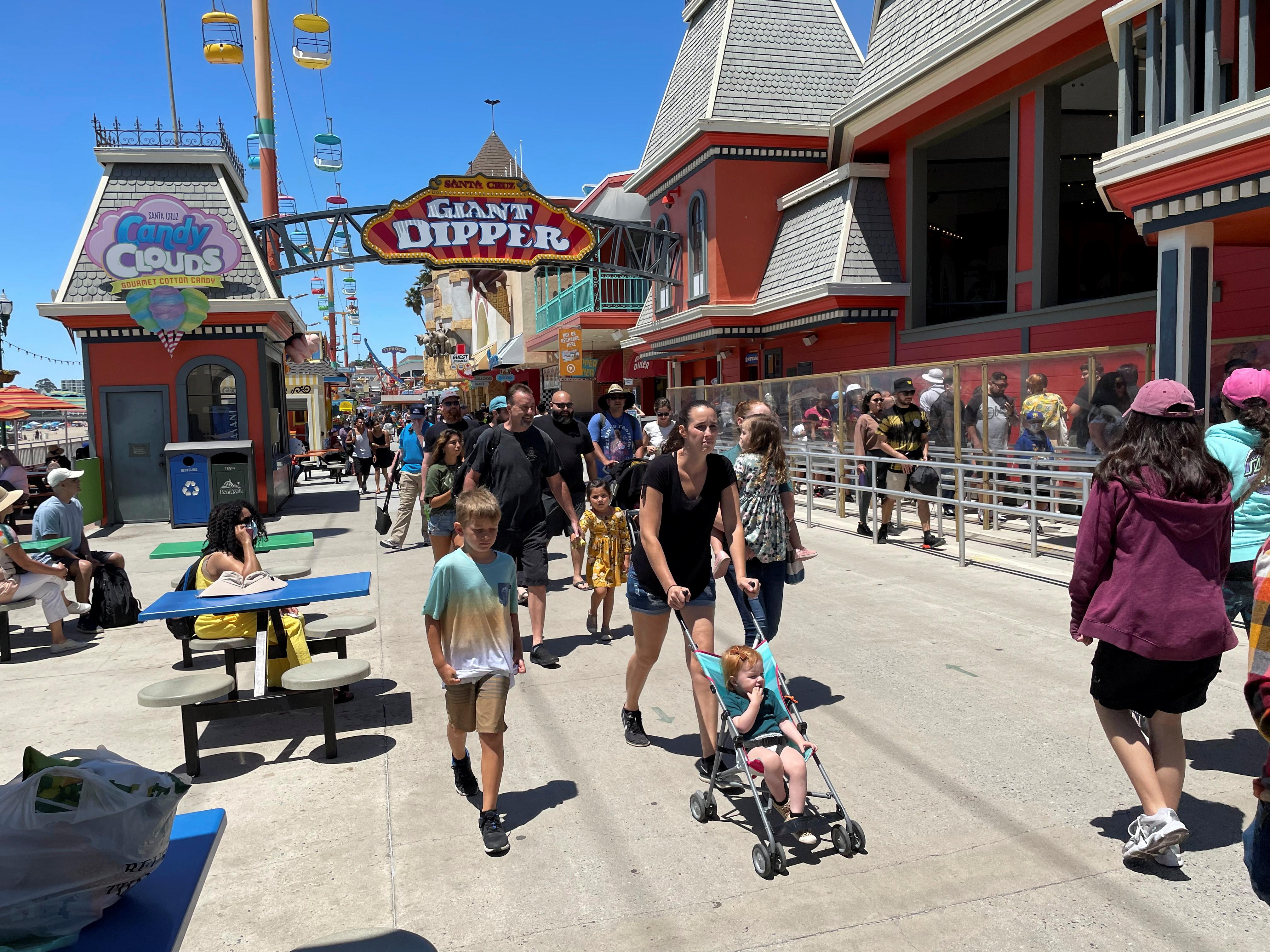 People walk past the Giant Dipper rollercoaster ride at the Santa Cruz Beach Boardwalk, amid the coronavirus disease (COVID-19) outbreak, in Santa Cruz, California, U.S. June 28, 2021. REUTERS/Nathan Frandino