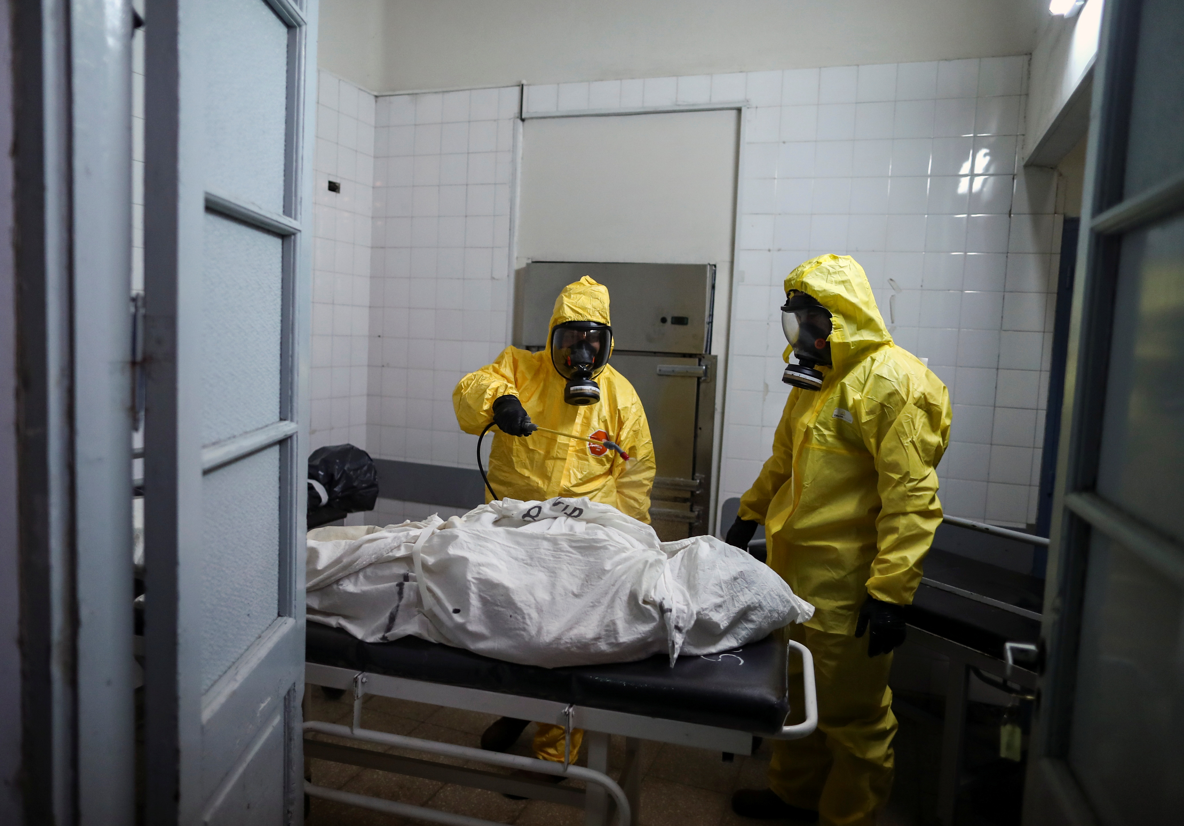 Gaston Rusichi and Oscar Oliva, members of the Department of High Risk Units (DUAR), disinfect a body of a person who died from the coronavirus disease (COVID-19) in a morgue, in Cordoba, Argentina, July 11, 2021. REUTERS/Agustin Marcarian