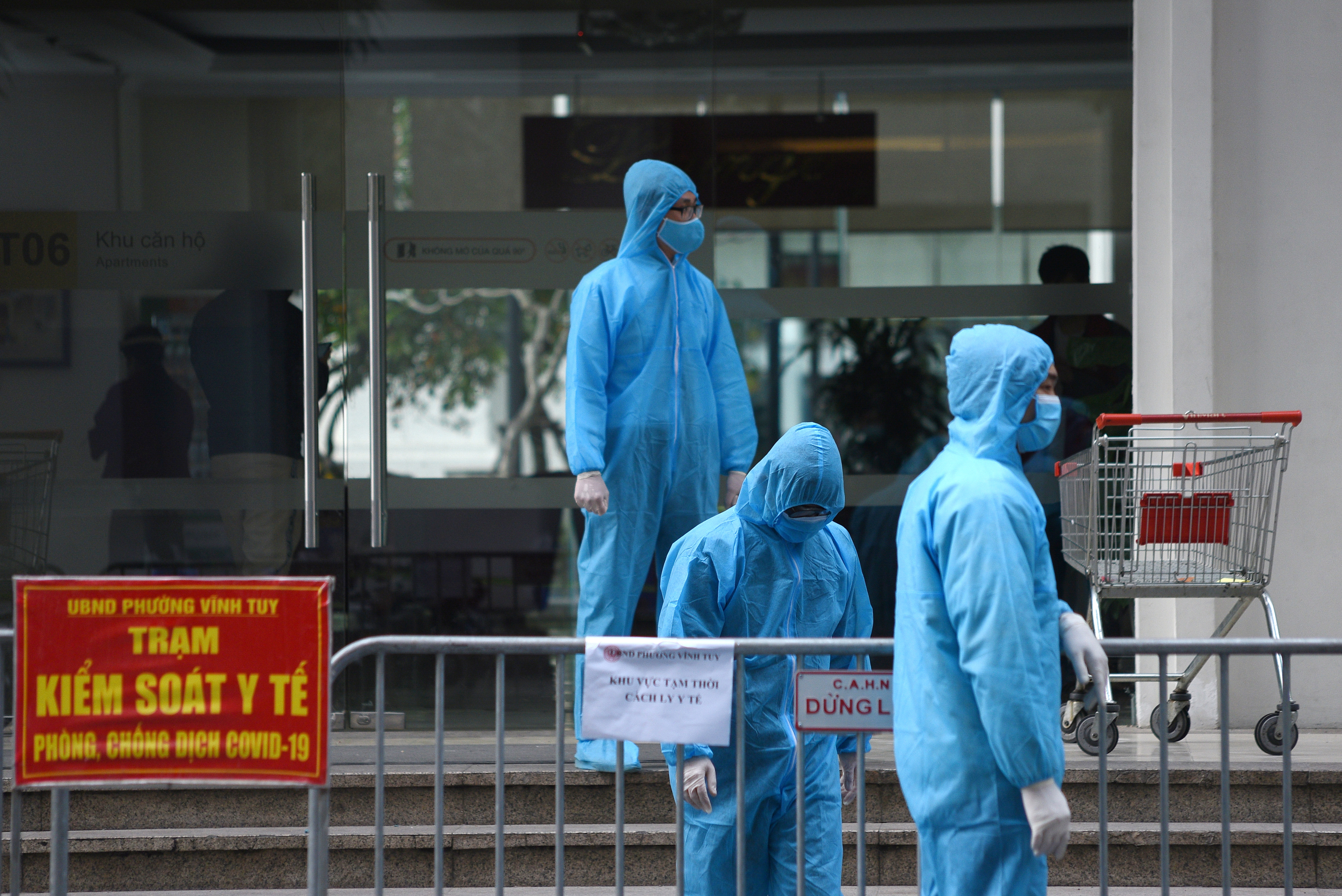 Medical workers in protective suits stand outside a quarantined building amid the coronavirus disease (COVID-19) outbreak in Hanoi, Vietnam, January 29, 2021. REUTERS/Thanh Hue