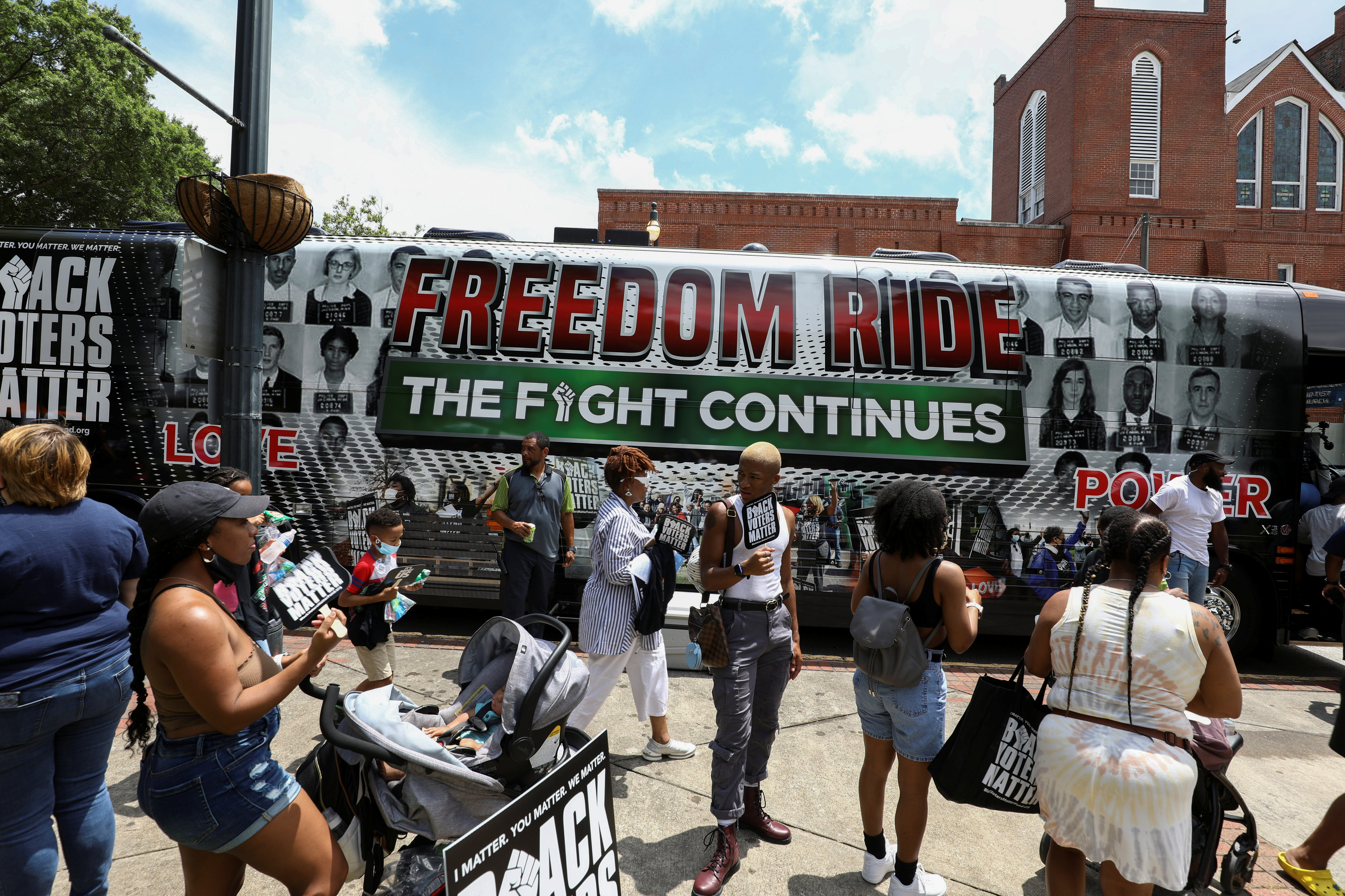 People gather in front of one of the tour buses during a stop on the Freedom Ride For Voting Rights at Ebenezer Baptist Church in Atlanta, Georgia, U.S. June 21, 2021.  REUTERS/Dustin Chambers