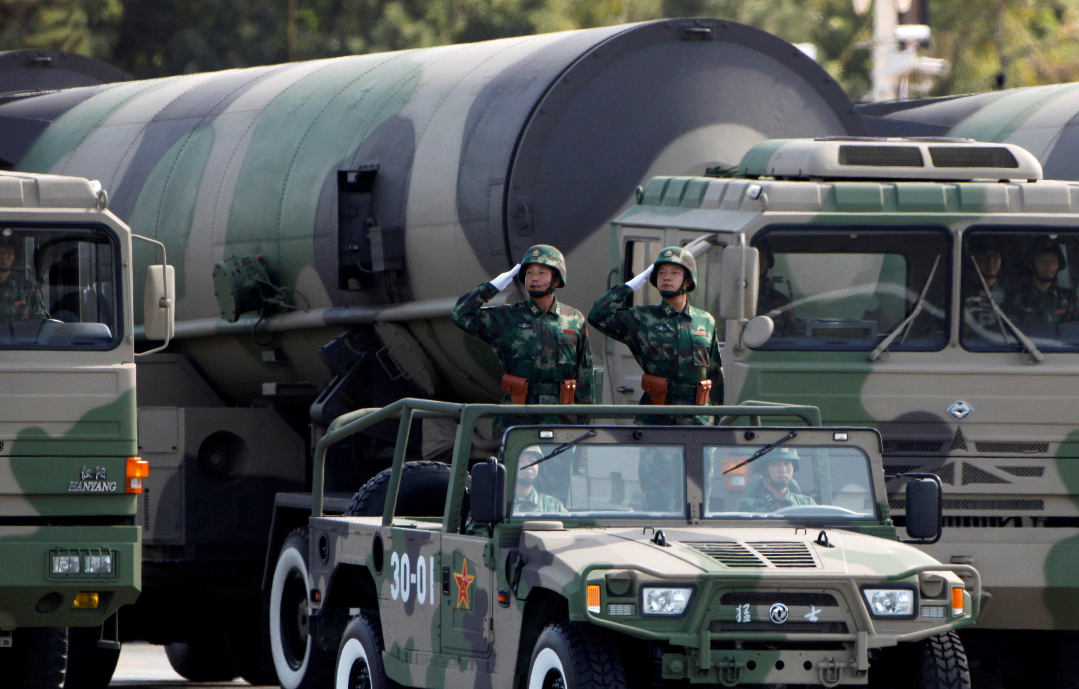 People's Liberation Army (PLA) soldiers salute in front of nuclear-capable missiles during a massive parade to mark the 60th anniversary of the founding of the People's Republic of China in Beijing October 1, 2009.  REUTERS/David Gray/File Photo