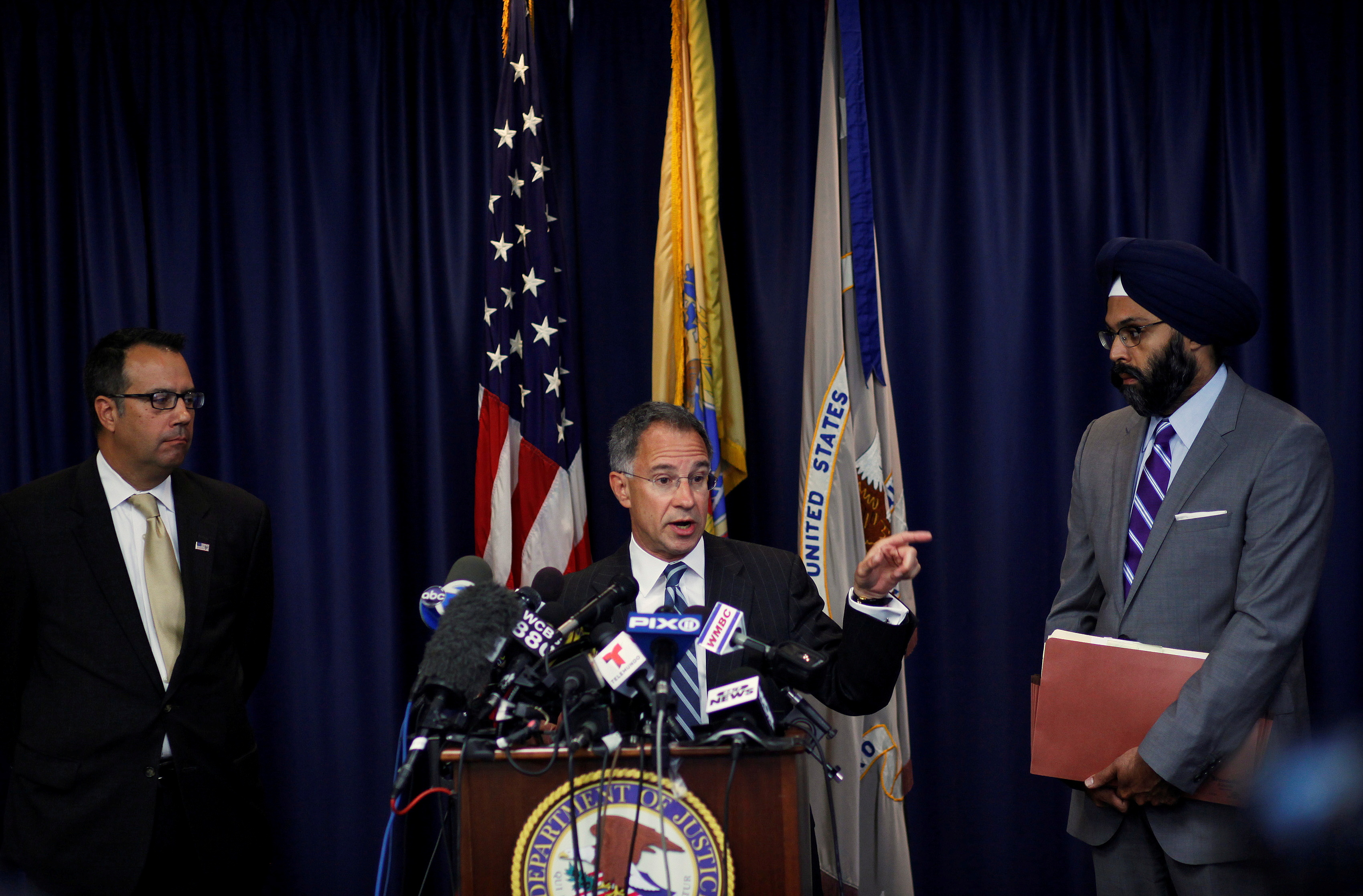 Gurbir Grewal (right) is seen in 2013 when he was assistant U.S. attorney in New Jersey. Also pictured are former New Jersey U.S. Attorney Paul  Fishman (center) and former U.S. Secret Service Special Agent James Mottola (at left), during a news conference in Newark, New Jersey, July 25, 2013.  REUTERS/Eduardo Munoz