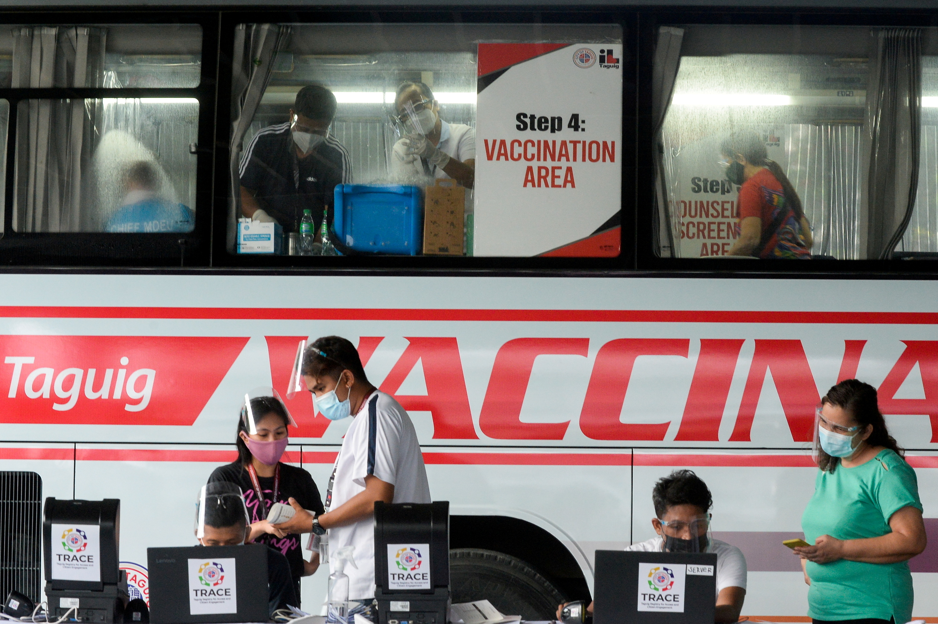 Health workers encode information and prepare vaccines against the coronavirus disease (COVID-19) at a mobile vaccination site in Taguig, Metro Manila, Philippines, May 21, 2021. REUTERS/Lisa Marie David