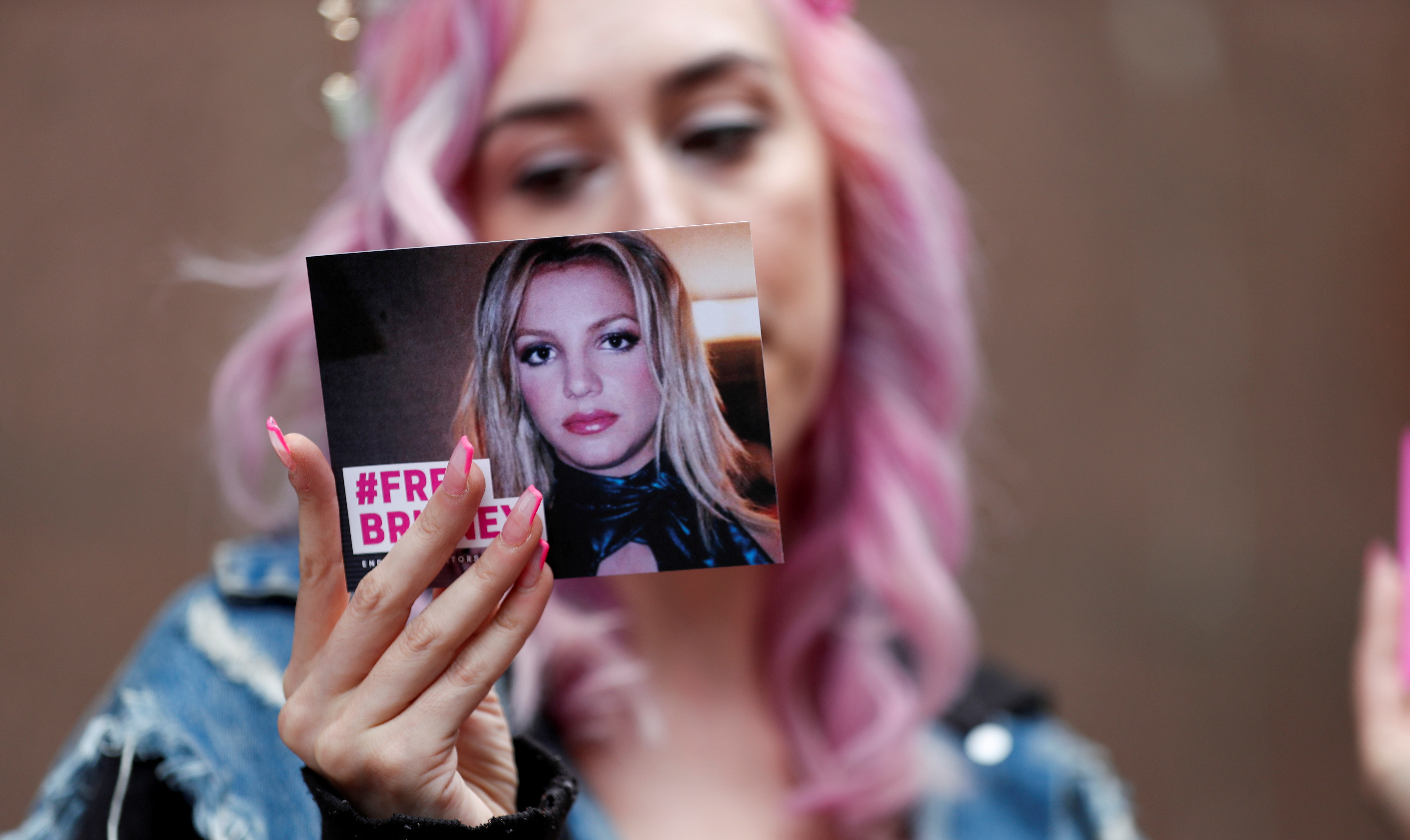 Supporter of pop star Britney Spears Melanie Mandarano holds a postcard on the day of a conservatorship case hearing at Stanley Mosk Courthouse in Los Angeles, California, U.S., July 26, 2021.  REUTERS/Mario Anzuoni