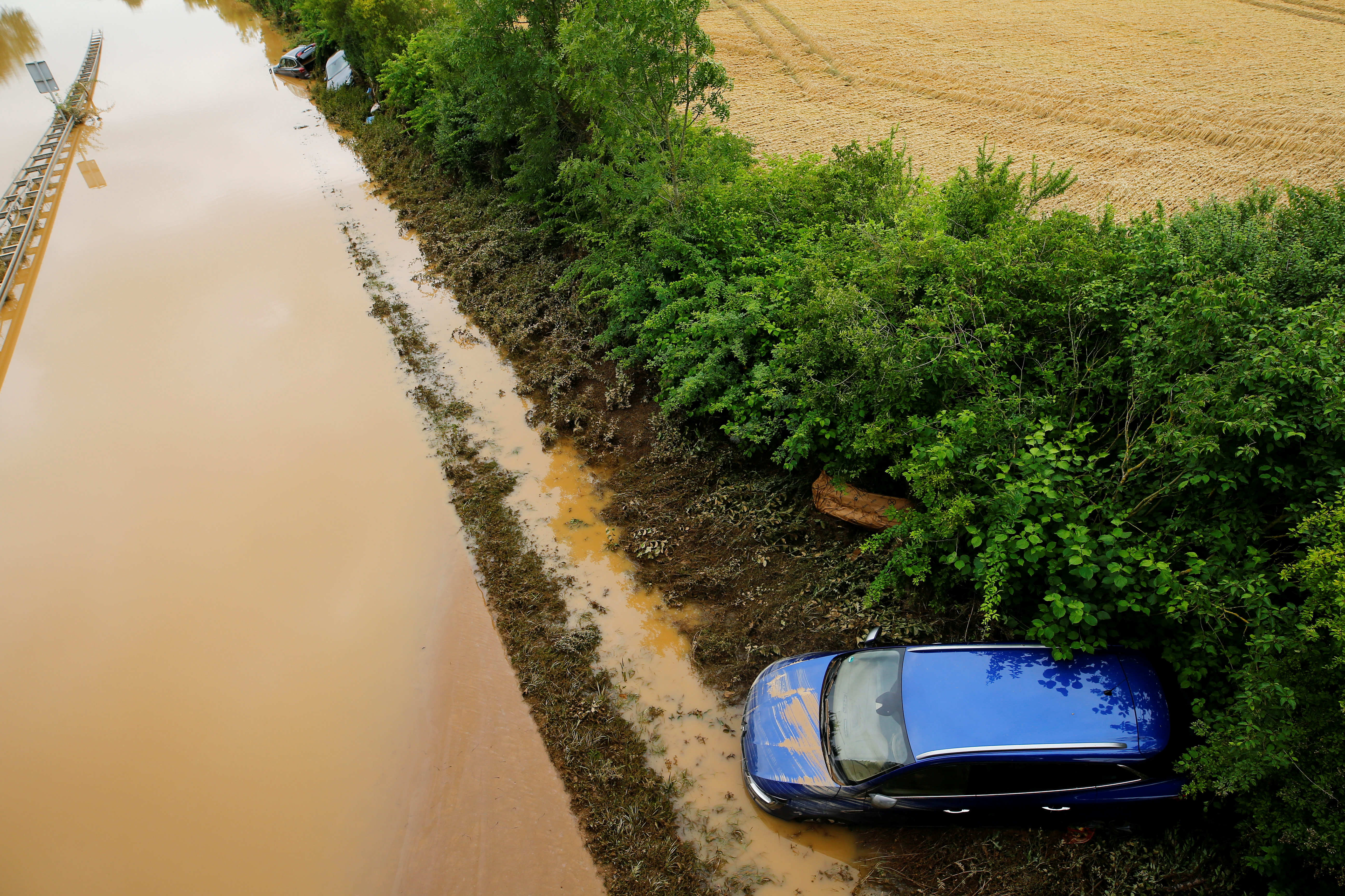 Damaged cars lie on a flooded street following heavy rainfalls in Erftstadt, Germany, July 16, 2021. REUTERS/Thilo Schmuelgen