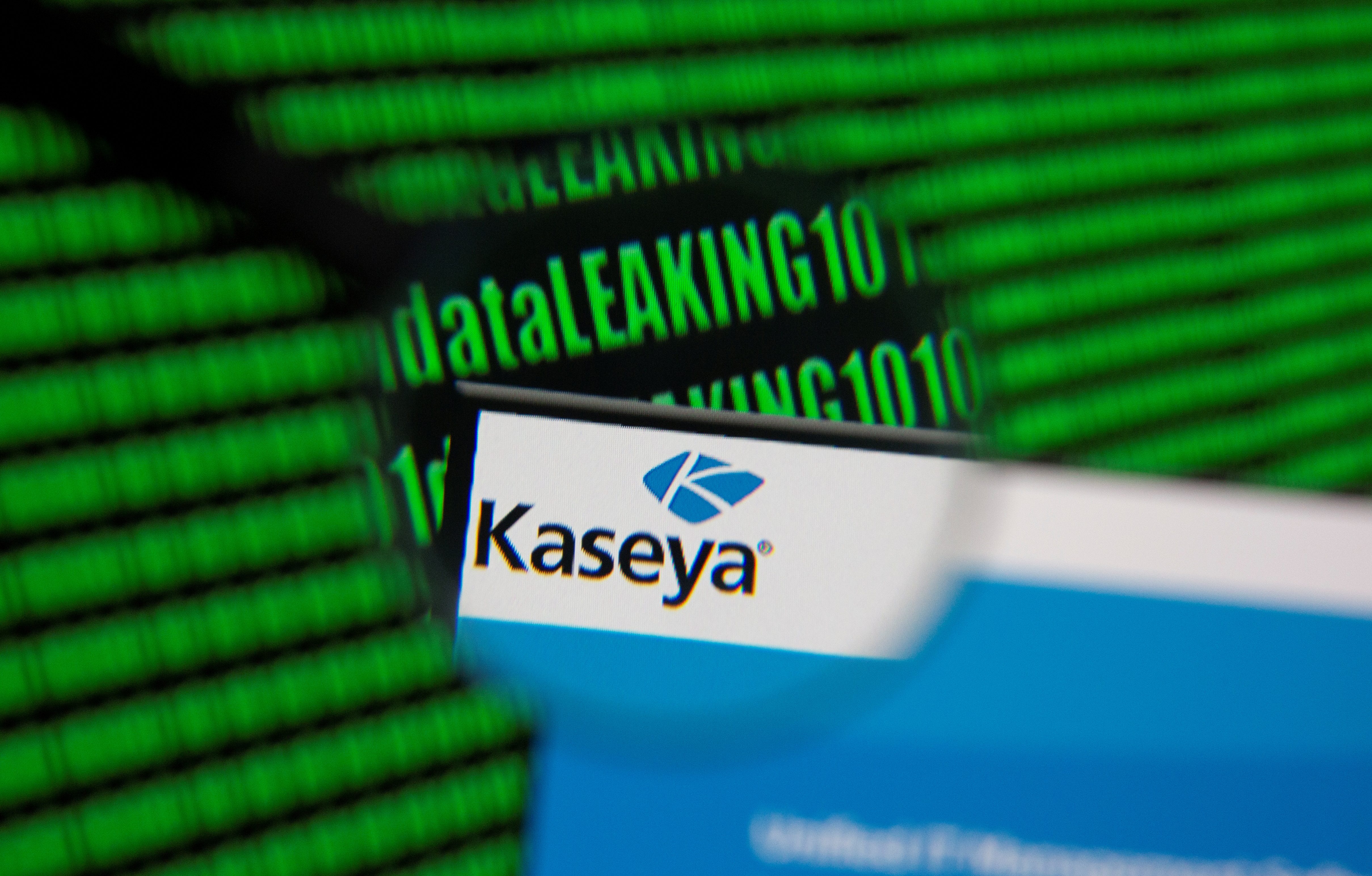 Kaseya's webpage is seen through magnifying glass in front of displayed binary code in this illustration taken, July 6, 2021. REUTERS/Dado Ruvic/Illustration