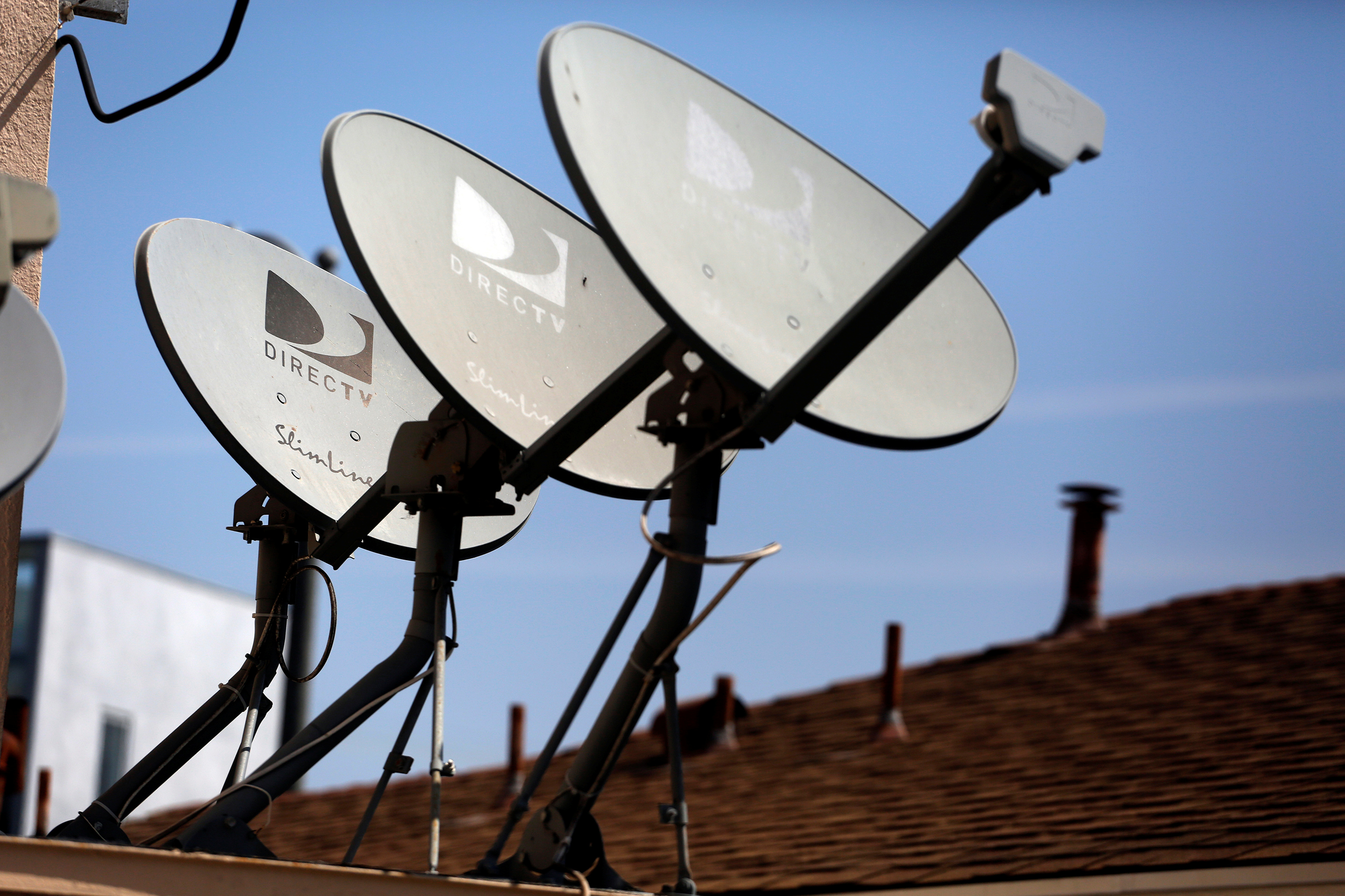 DirecTV satellite dishes are seen on an apartment roof in Los Angeles, California in this file photo taken May 18, 2014.  REUTERS/Jonathan Alcorn