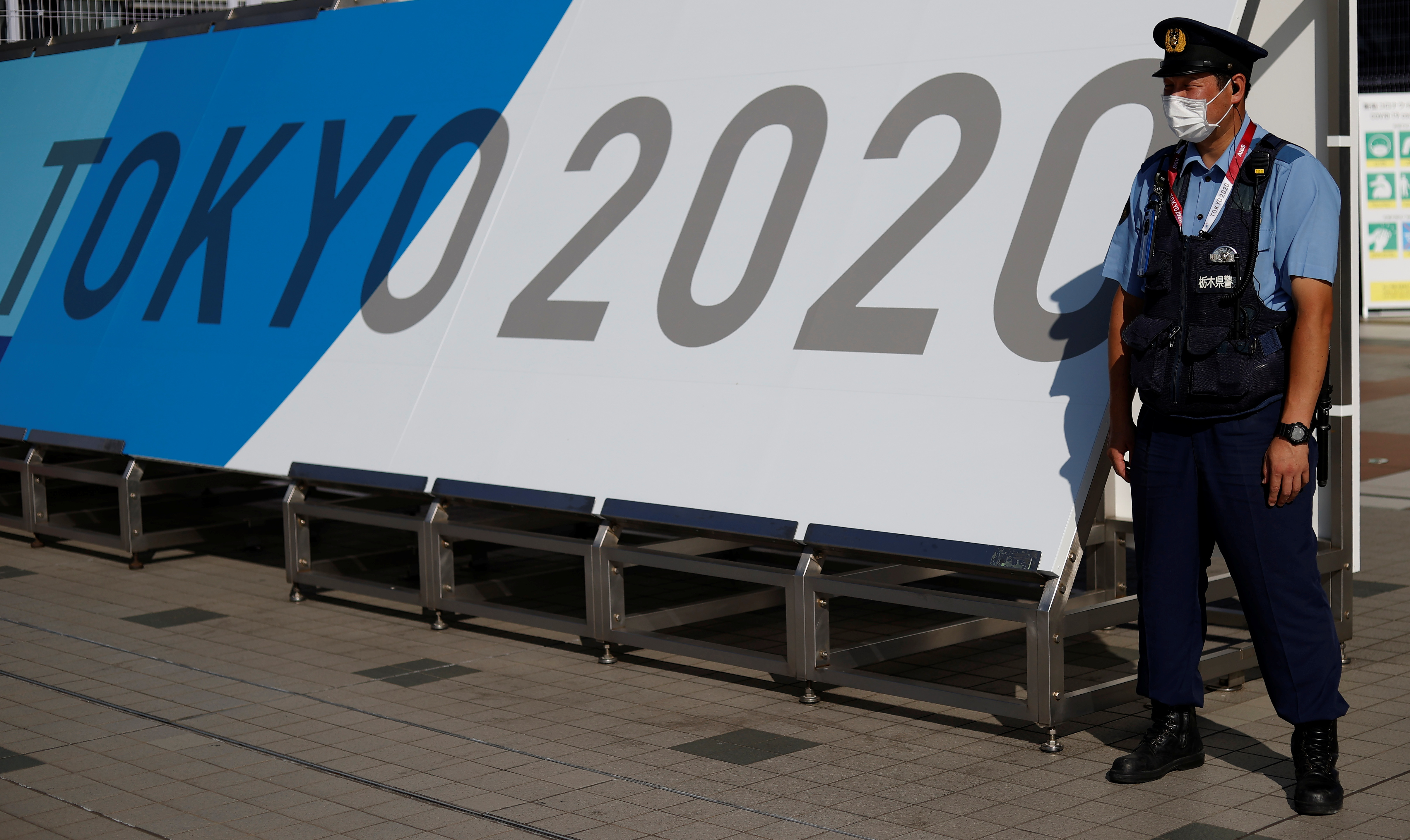 A police officer wearing a face mask stands near the entrance of the Main Press Centre, ahead of the Tokyo 2020 Olympic Games, in Tokyo, Japan, July 19, 2021. REUTERS/Phil Noble