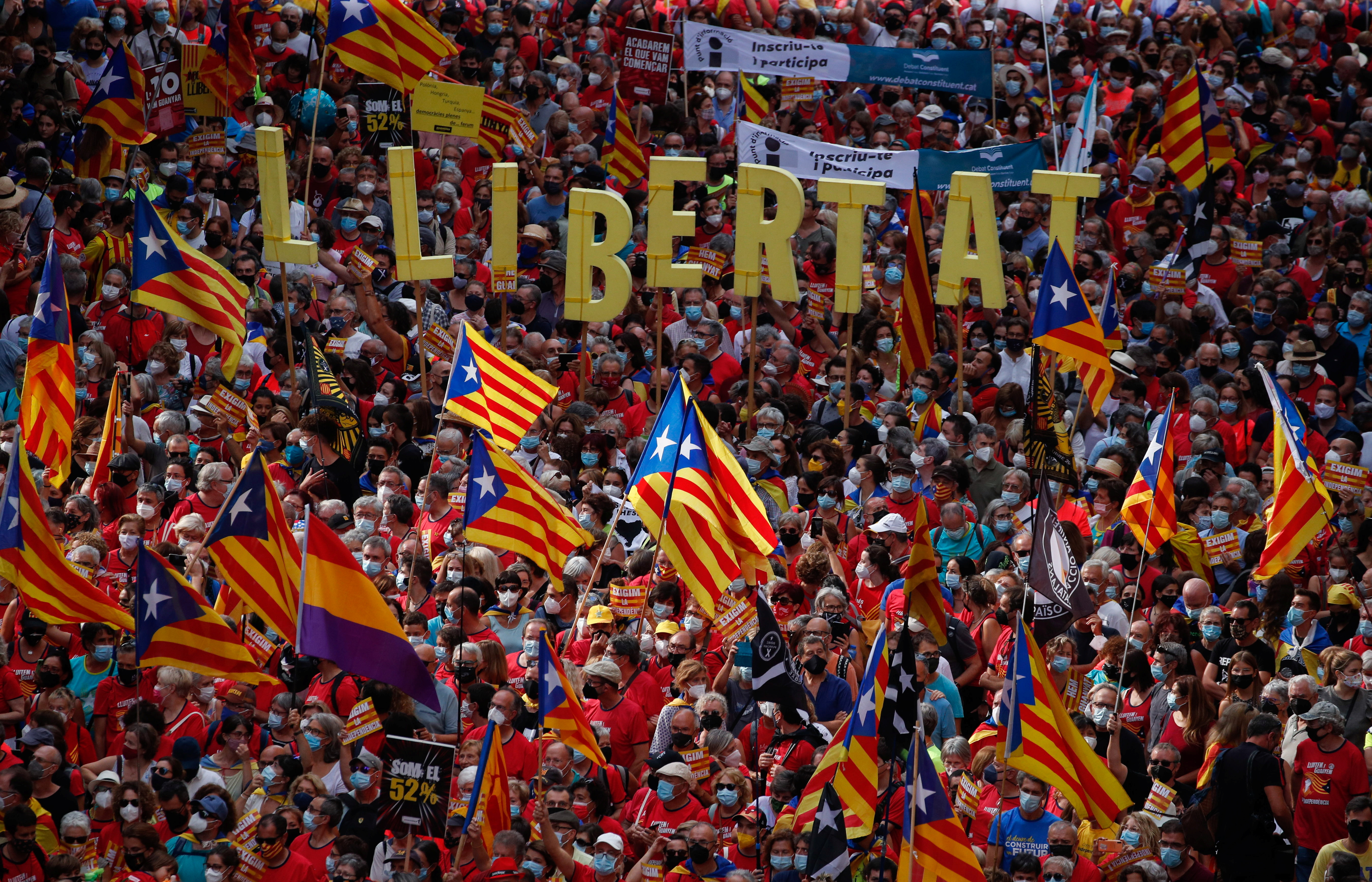 People hold up Estelada flags (Catalan separatist flag) during Catalonia's national day, 'La Diada', in Barcelona, Spain, September 11, 2021. The banner reads