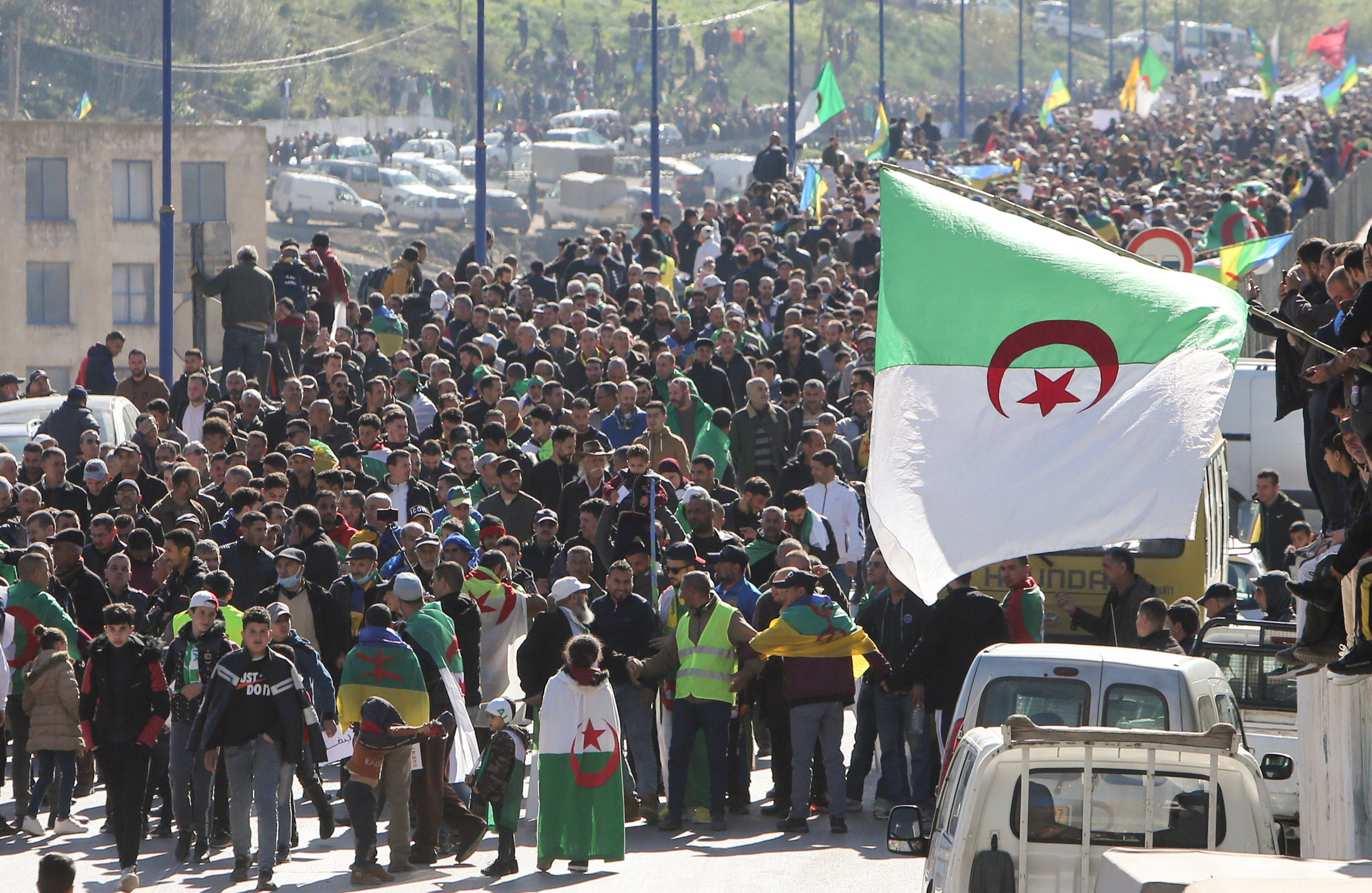 Demonstrators carry national flags as they gather in the town of Kherrata, marking two years since the start of a mass protest movement there demanding political change, Algeria February 16, 2021. REUTERS/Ramzi Boudina