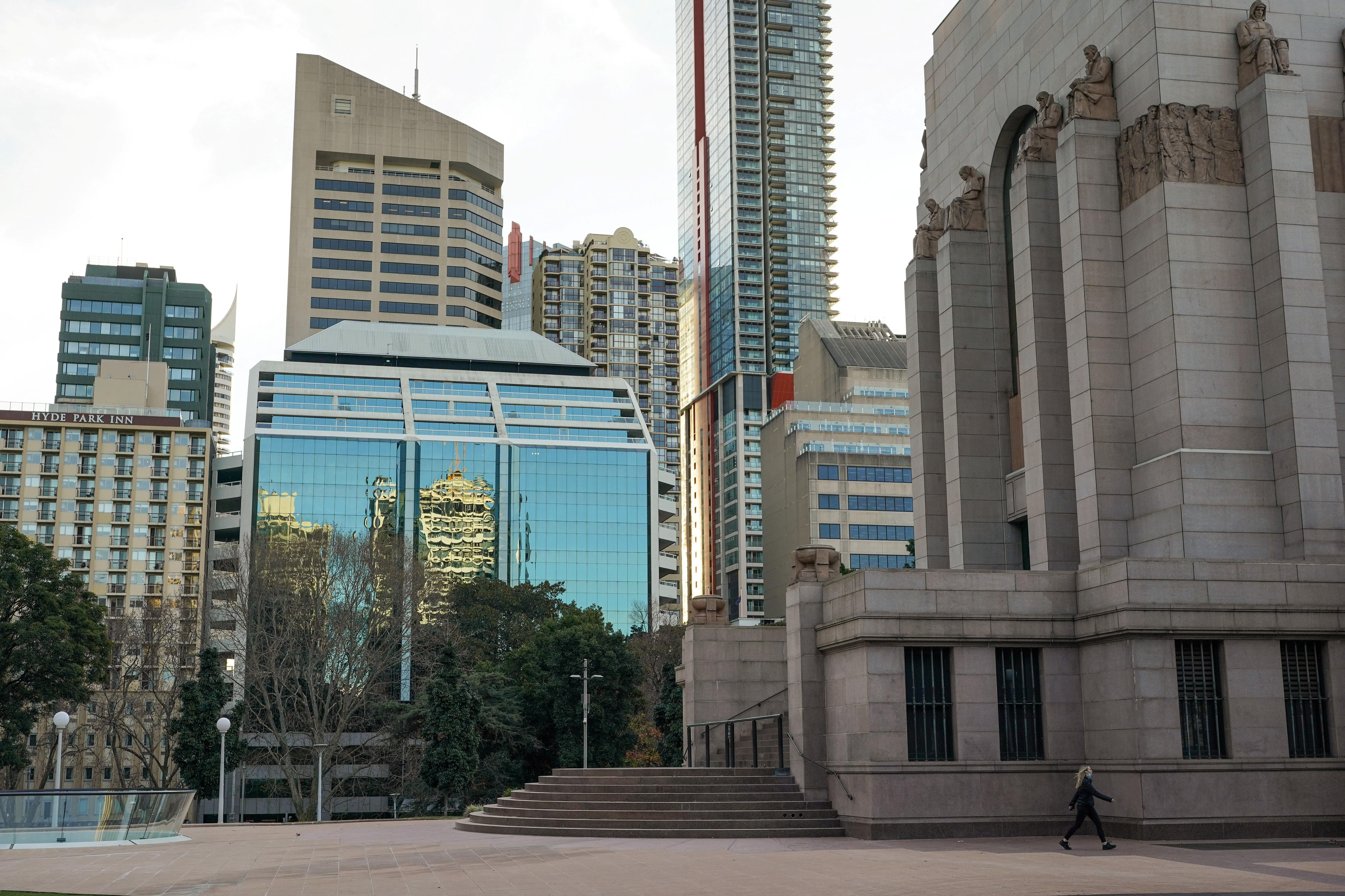 A lone woman walks past the Anzac Memorial as Hyde Park is mostly devoid of people during a lockdown to curb the spread of a coronavirus disease (COVID-19) outbreak in Sydney, Australia, July 22, 2021.  REUTERS/Loren Elliott/File Photo