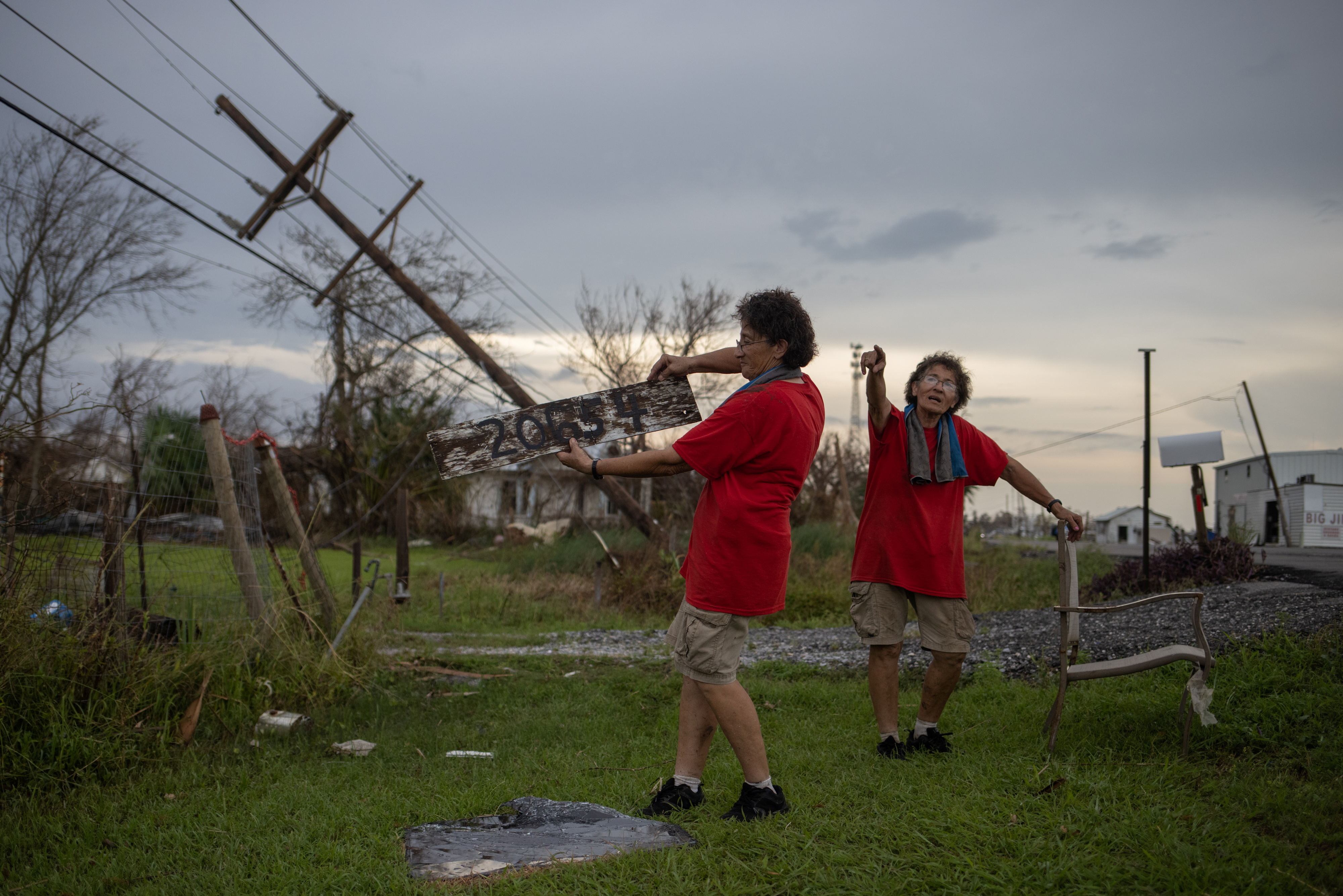 Bridget Serigny, 66, holds together the broken sign of their home address as her twin sister Rosalie points towards where they found it in the aftermath of Hurricane Ida in Golden Meadow, Louisiana, U.S., September 1, 2021.  REUTERS/Adrees Latif