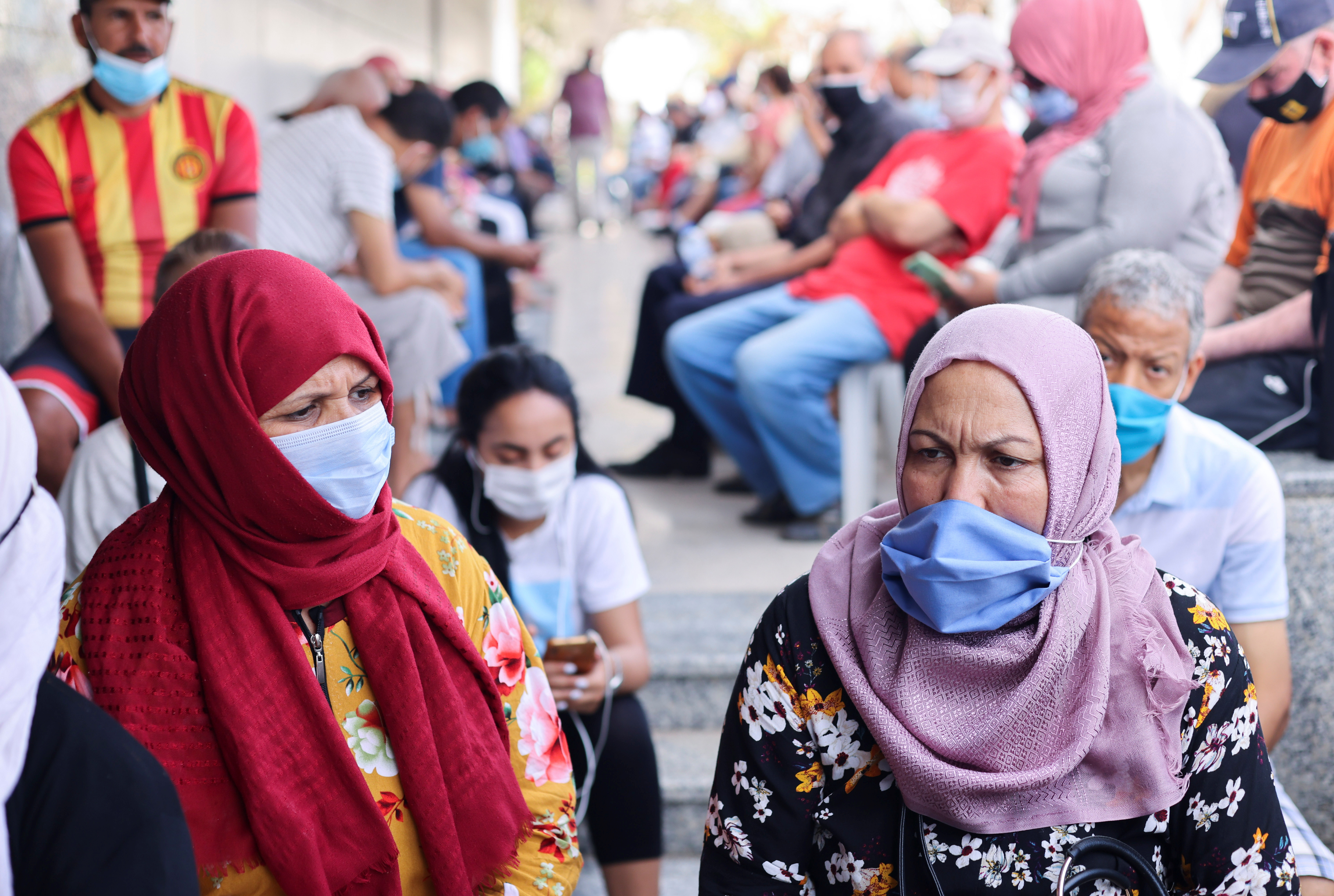 People wearing masks wait to receive the COVID-19 vaccine at a vaccination center in Tunis, Tunisia August 1, 2021. REUTERS/Ammar Awad