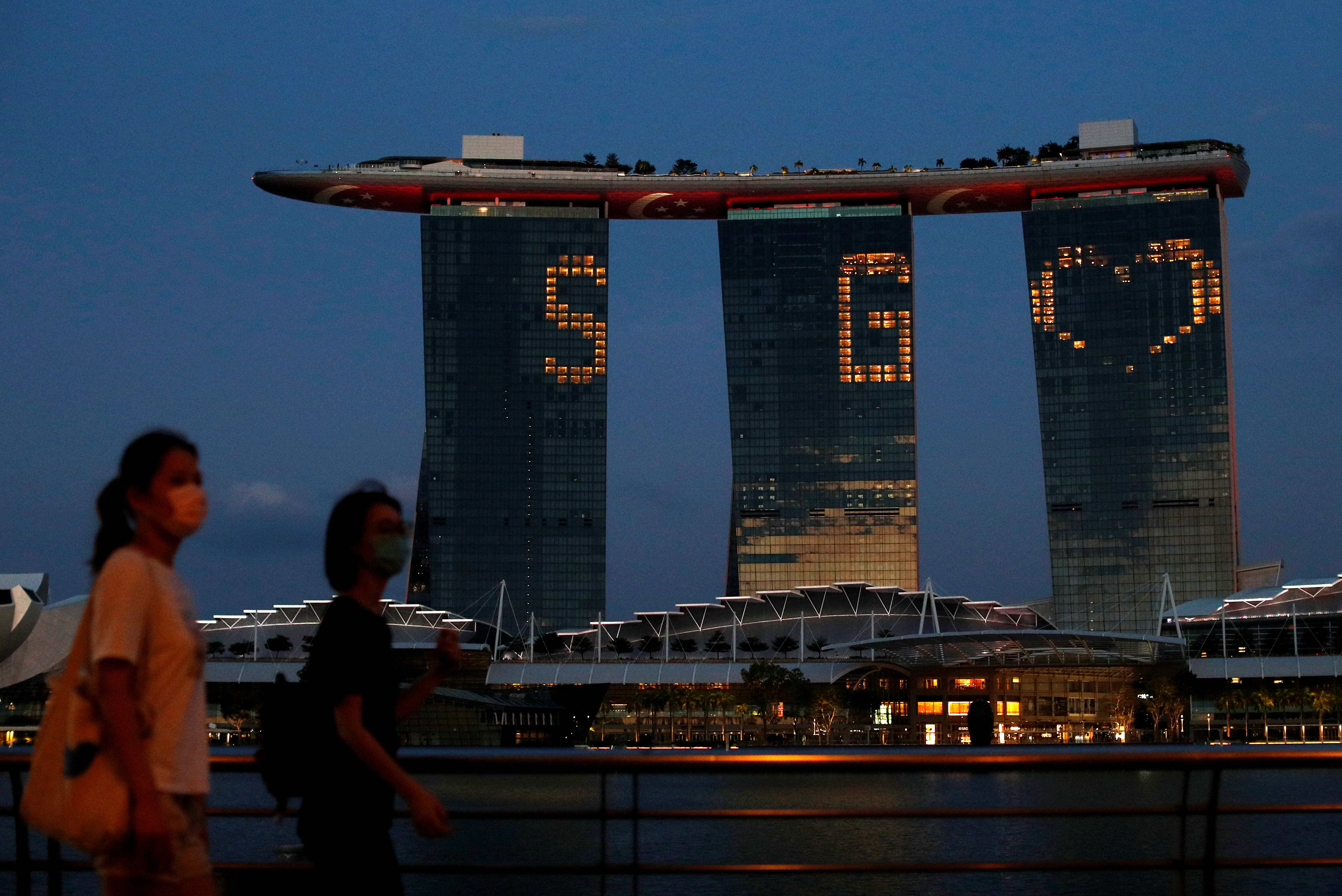 The Marina Bay Sands integrated resort lights up in tribute to the healthcare workers and people staying home to curb the spread of the coronavirus disease (COVID-19) outbreak in Singapore, April 10, 2020. REUTERS/Edgar Su
