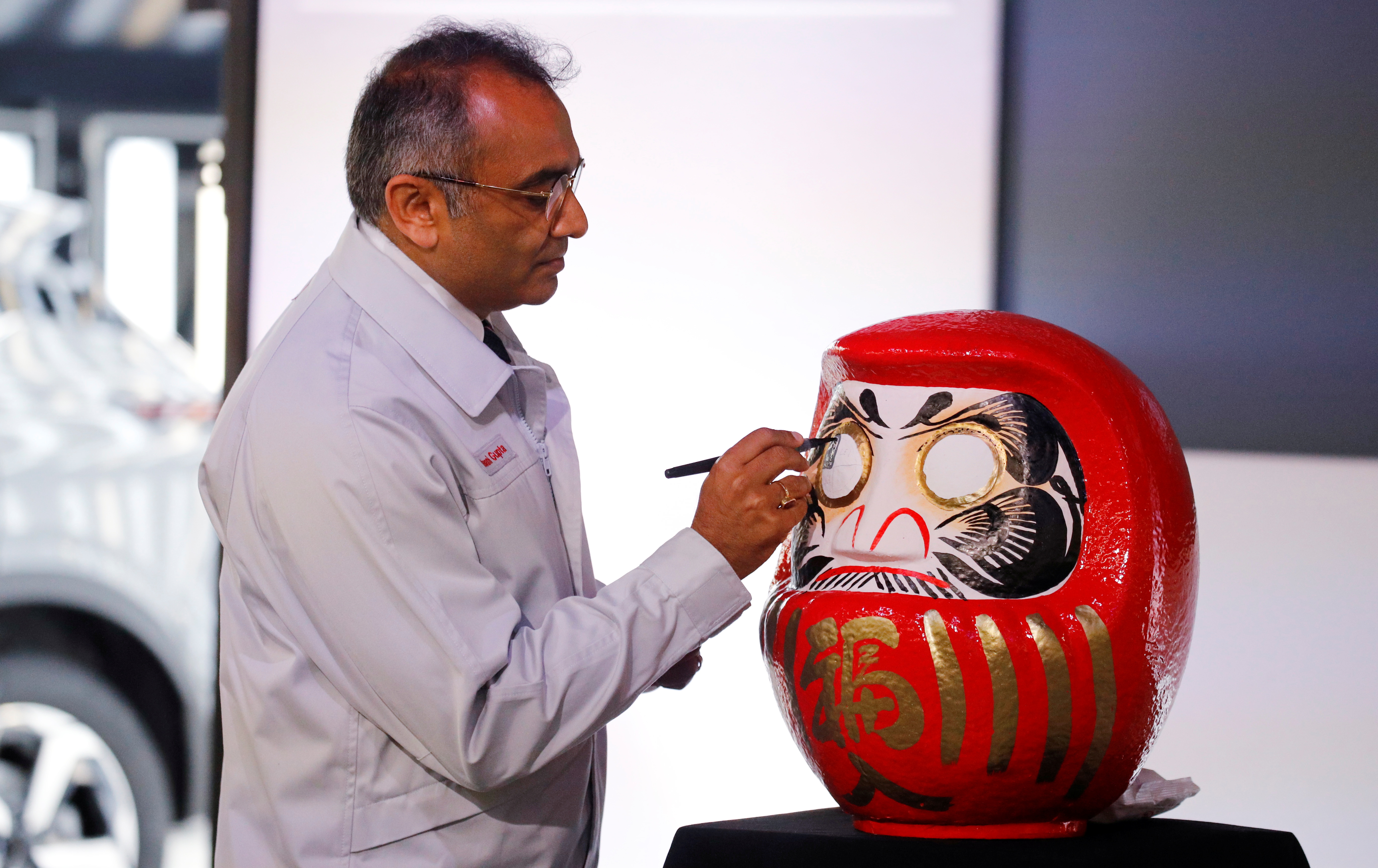 Ashwani Gupta, Nissan's chief operating officer, colours in the eye of a Duruma doll, a Japanese symbol of good luck, following a news conference at Nissan's Sunderland plant, Britain, July 1, 2021. REUTERS/Phil Noble