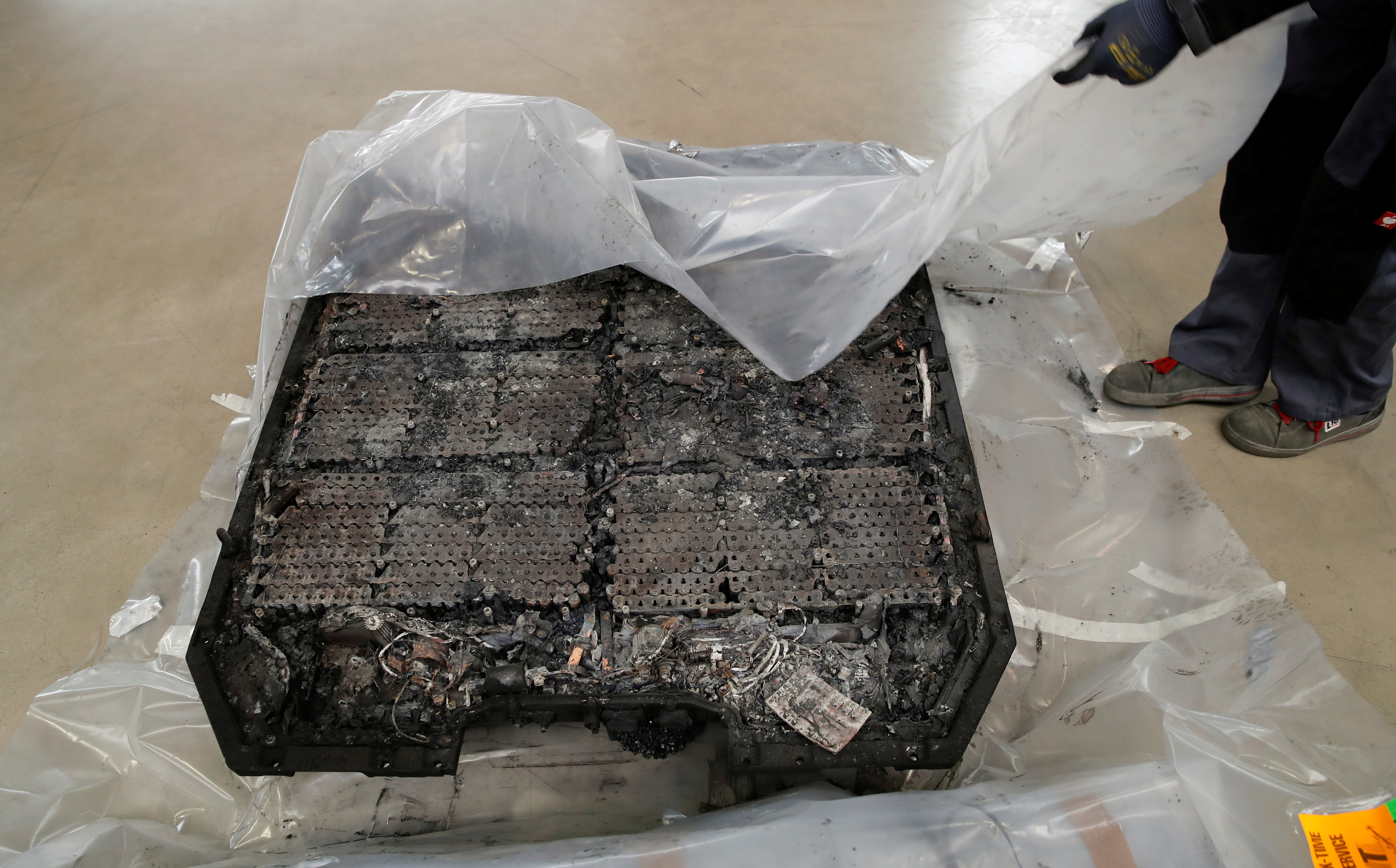 A technician unpacks a completely burned Lithium-ion car battery before its dismantling by the German recycling firm Accurec in Krefeld, Germany, November 16, 2017. REUTERS/Wolfgang Rattay