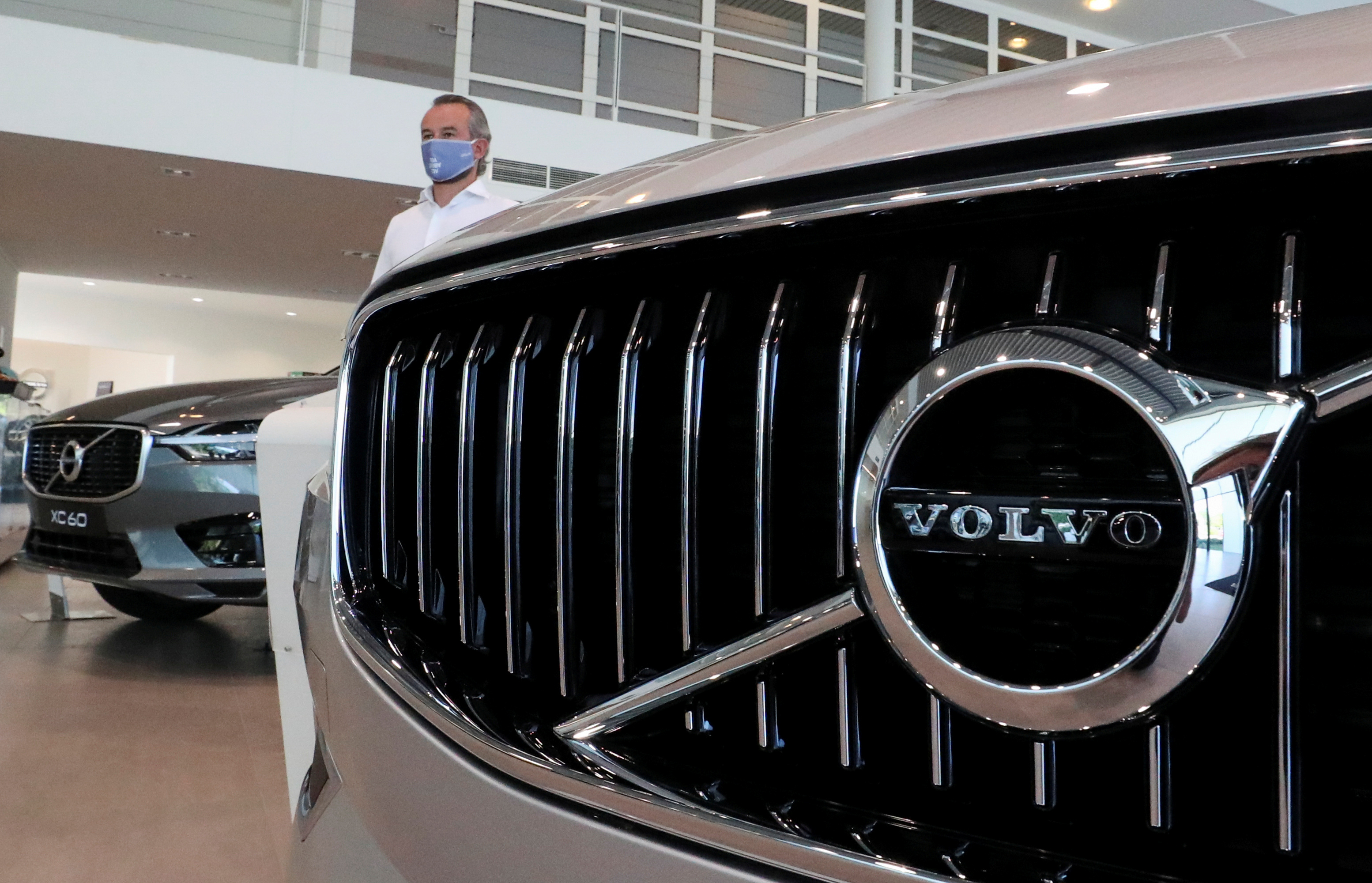 An employee at a Volvo car dealer, wearing a protective mask is seen in the showroom in Brussels, Belgium May 28, 2020. REUTERS/Yves Herman