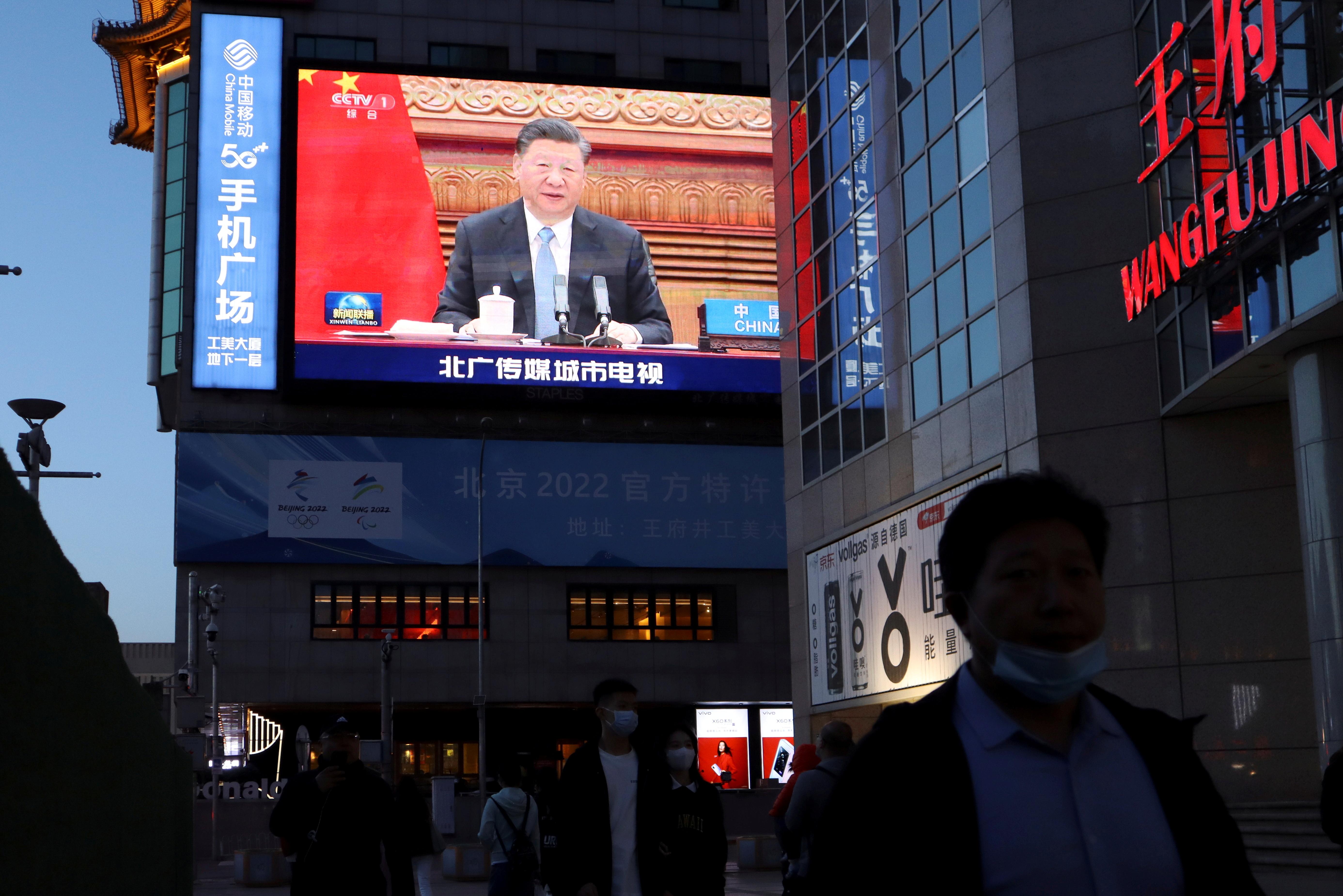 'n Reuse-skerm wys nuusmateriaal van Chinese president Xi Jinping wat 'n videoberaad oor klimaatsverandering saam met die Duitse kanselier Angela Merkel en die Franse president Emmanuel Macron bywoon by 'n winkelstraat in Beijing, China, 16 April 2021. REUTERS/Florence Lo