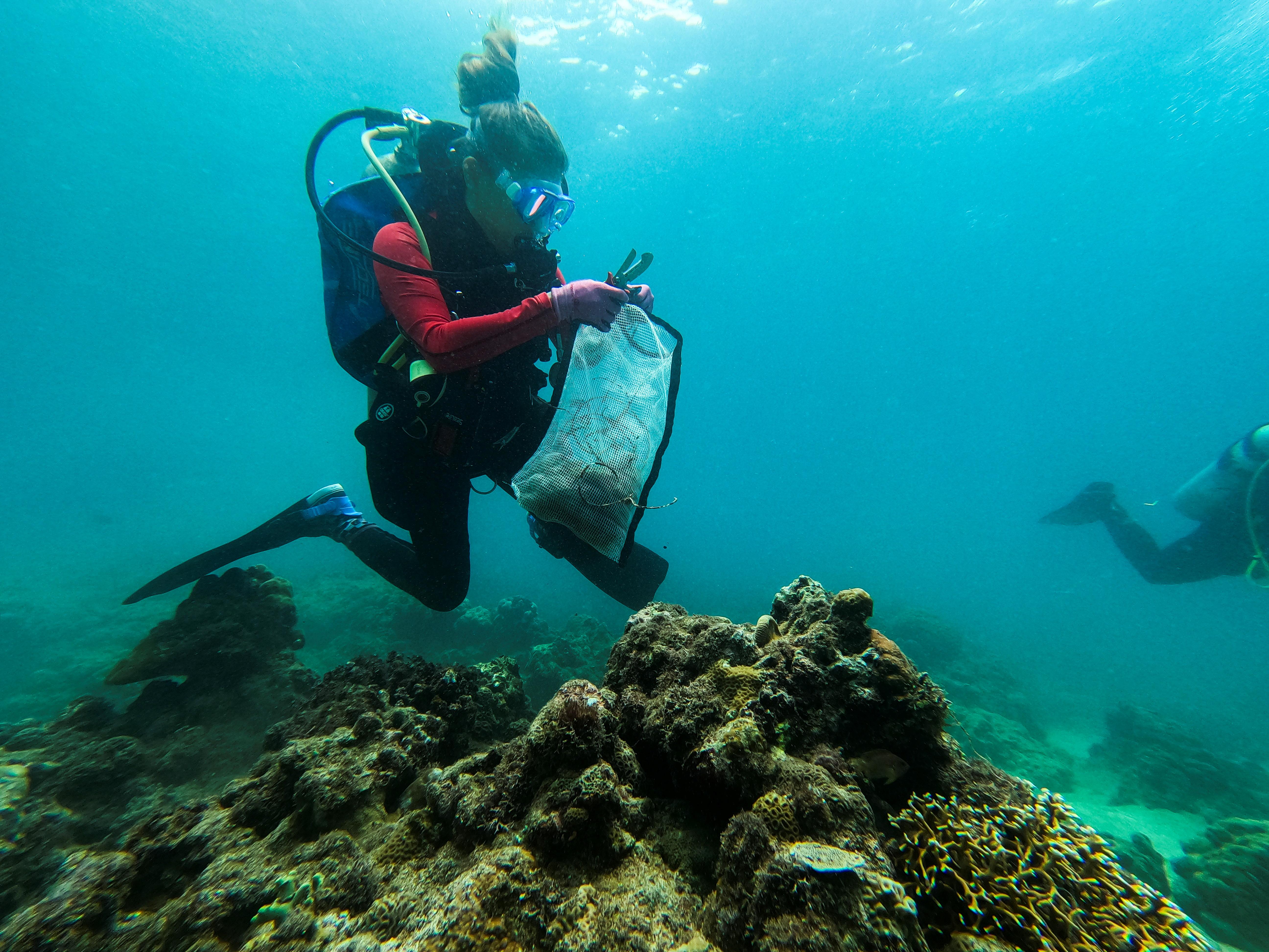 Huấn luyện viên lặn Carmela Sevilla cầm một túi lưới chứa đầy rác trong chuyến đi dọn dẹp dưới nước ở Bauan, tỉnh Batangas, Philippines, ngày 18 tháng 9 năm 2021. REUTERS / Peter Blaza