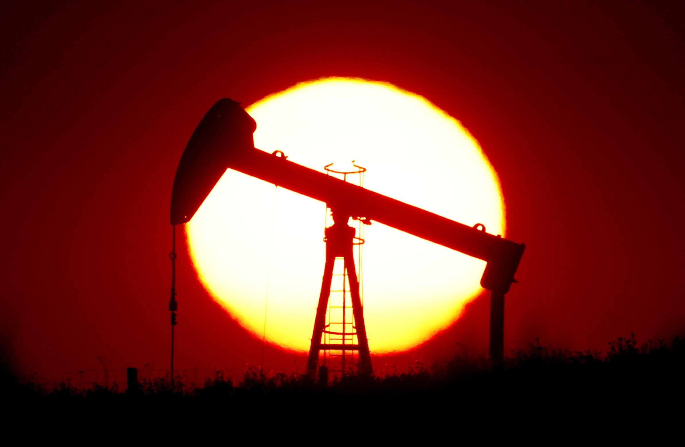 The sun sets behind an oil pump outside Saint-Fiacre, near Paris, France September 17, 2019. REUTERS/Christian Hartmann/File Photo