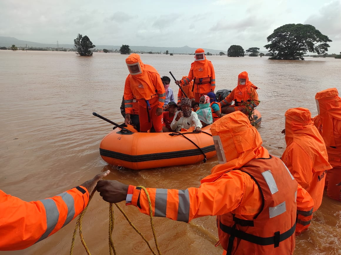 Members of National Disaster Response Force (NDRF) evacuate people from a flooded area to safer places in Balinge village, Kolhapur district, in the western Indian state of Maharashtra, India, July 25, 2021. National Disaster Response Force/Handout via REUTERS