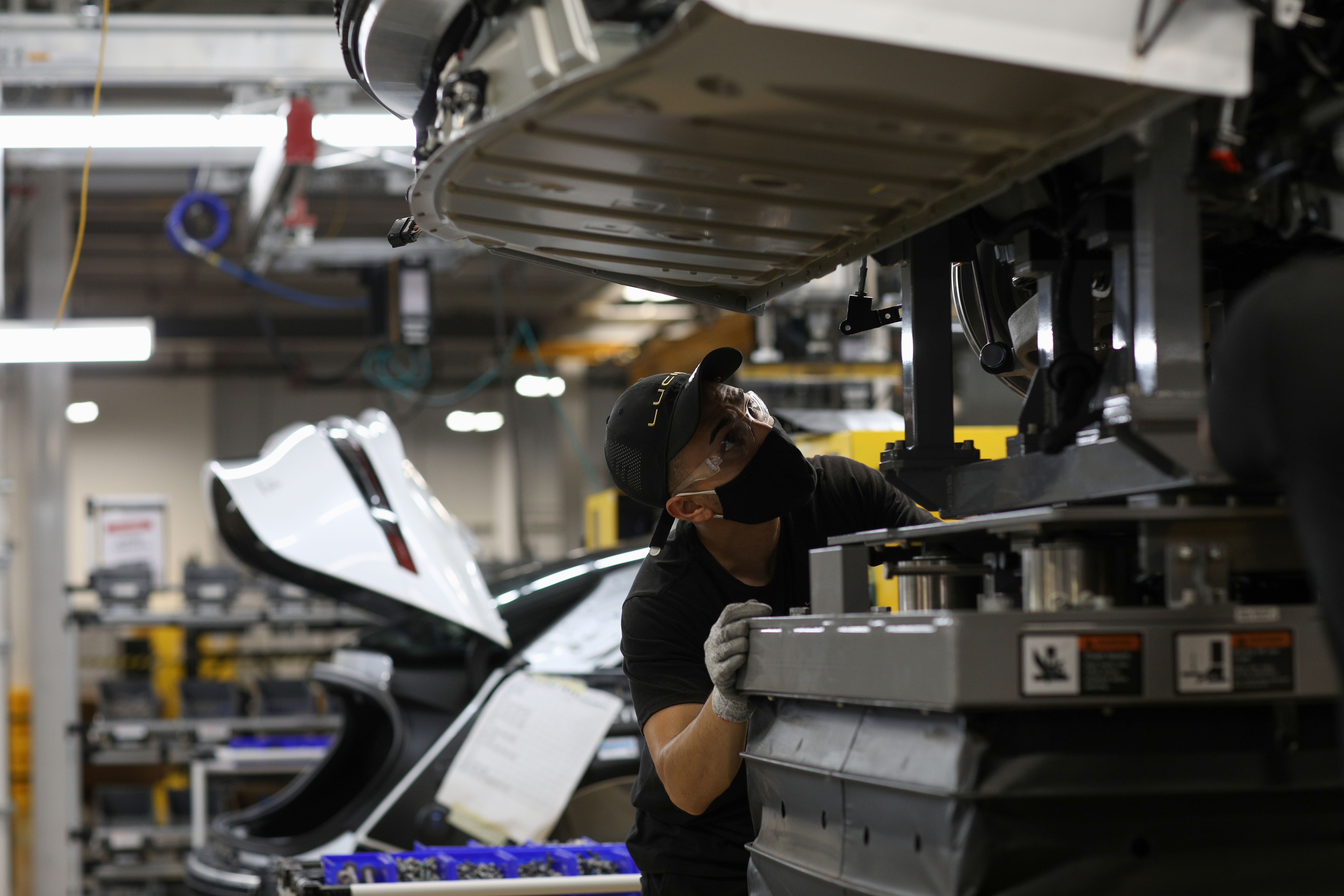 A worker looks to marry the body structure with the battery pack and the front and rear sub frames as they assemble electric vehicles at the Lucid Motors plant in Casa Grande, Arizona, U.S. September 28, 2021.  REUTERS/Caitlin O'Hara