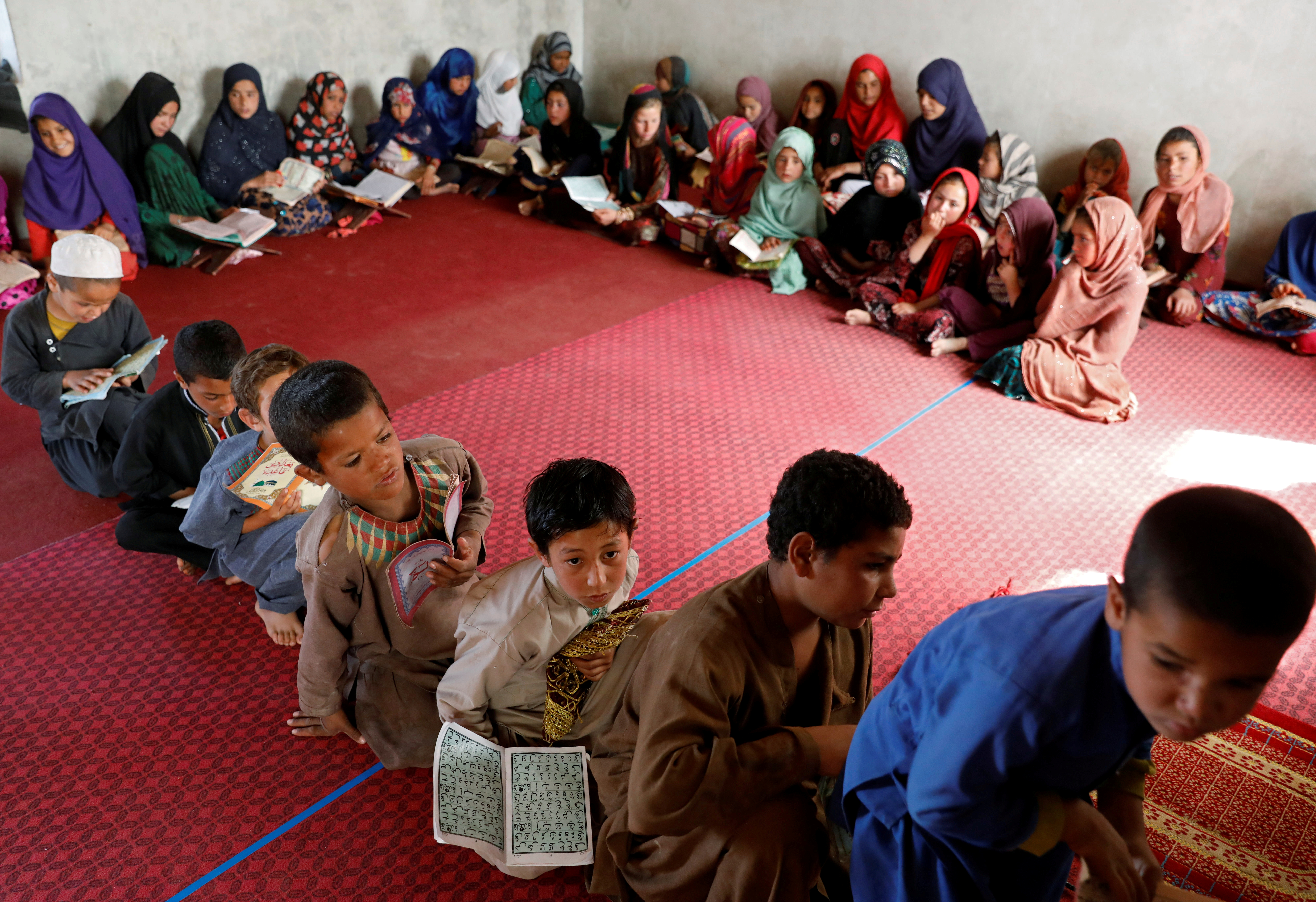 Internally displaced Afghan children read the Koran at a mosque, amidst the spread of the coronavirus disease (COVID-19) during the holy fasting month of Ramadan, in Kabul, Afghanistan May 10, 2020. REUTERS/Mohammad Ismail     TPX IMAGES OF THE DAY