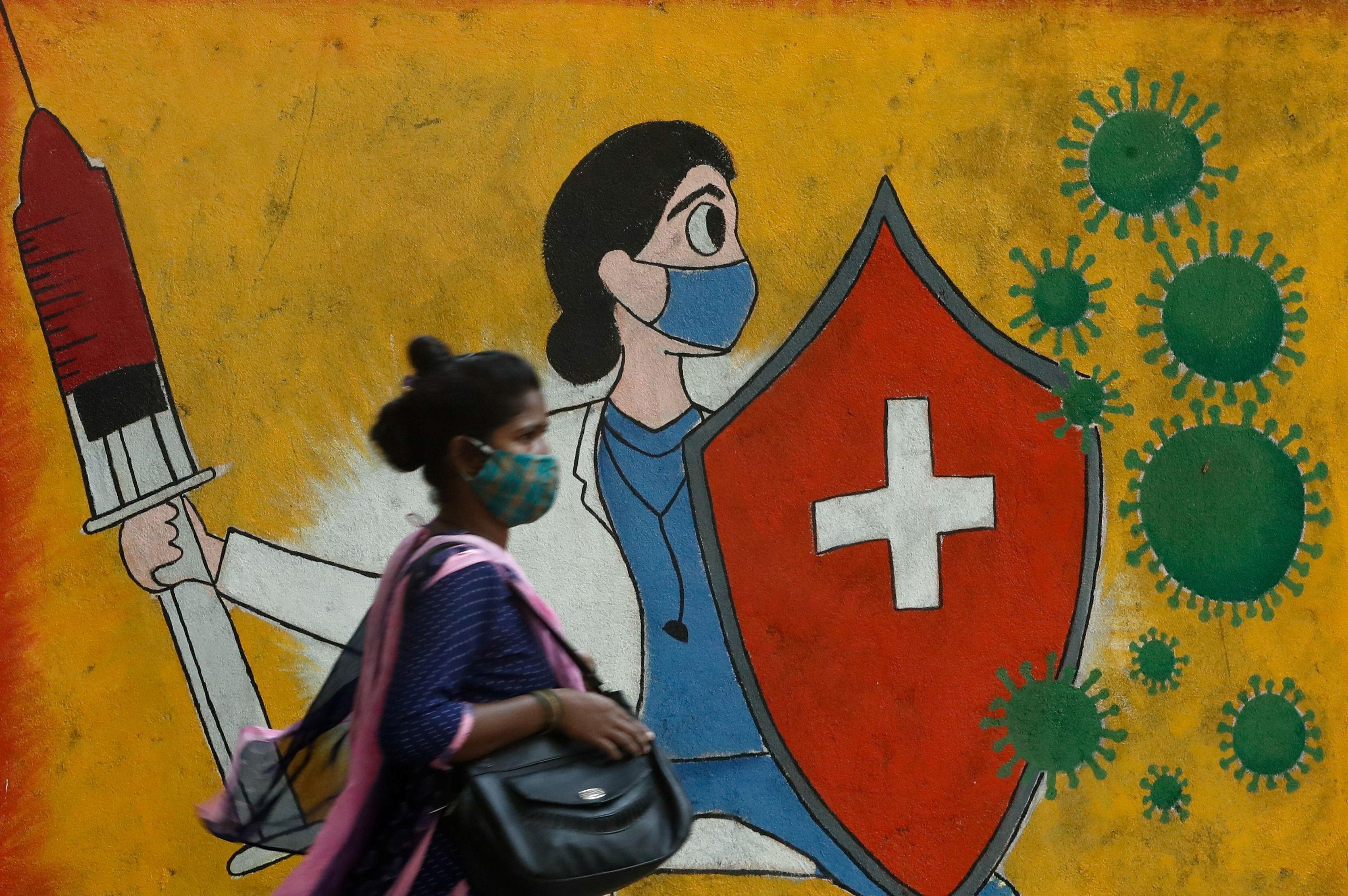 A woman walks past a graffiti on a street, amidst the spread of the coronavirus disease (COVID-19) in Mumbai, India, May 10, 2021. REUTERS/Francis Mascarenhas